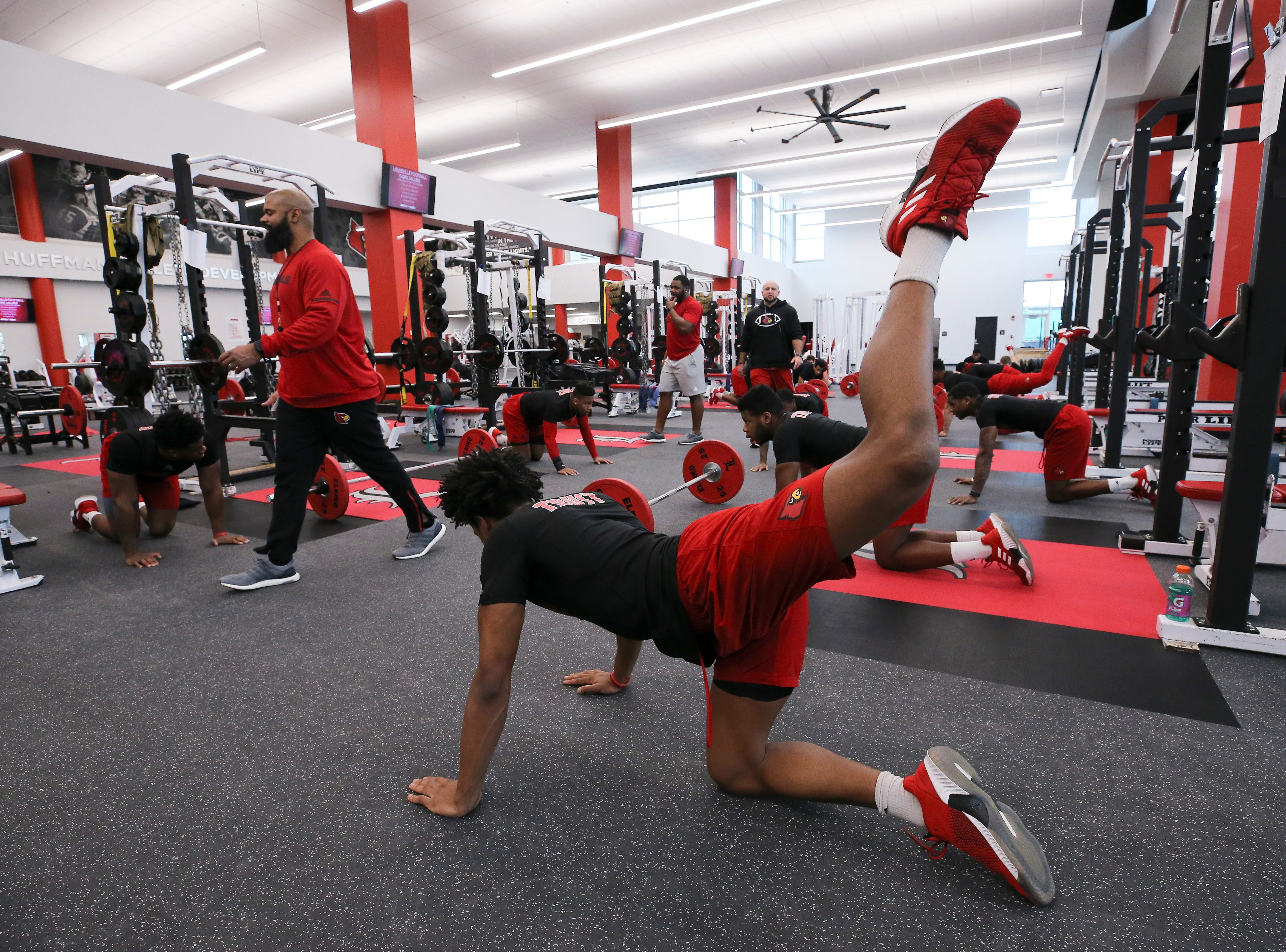 The U of L football team stretches before strength and conditioning at the Schnellenberger Complex.