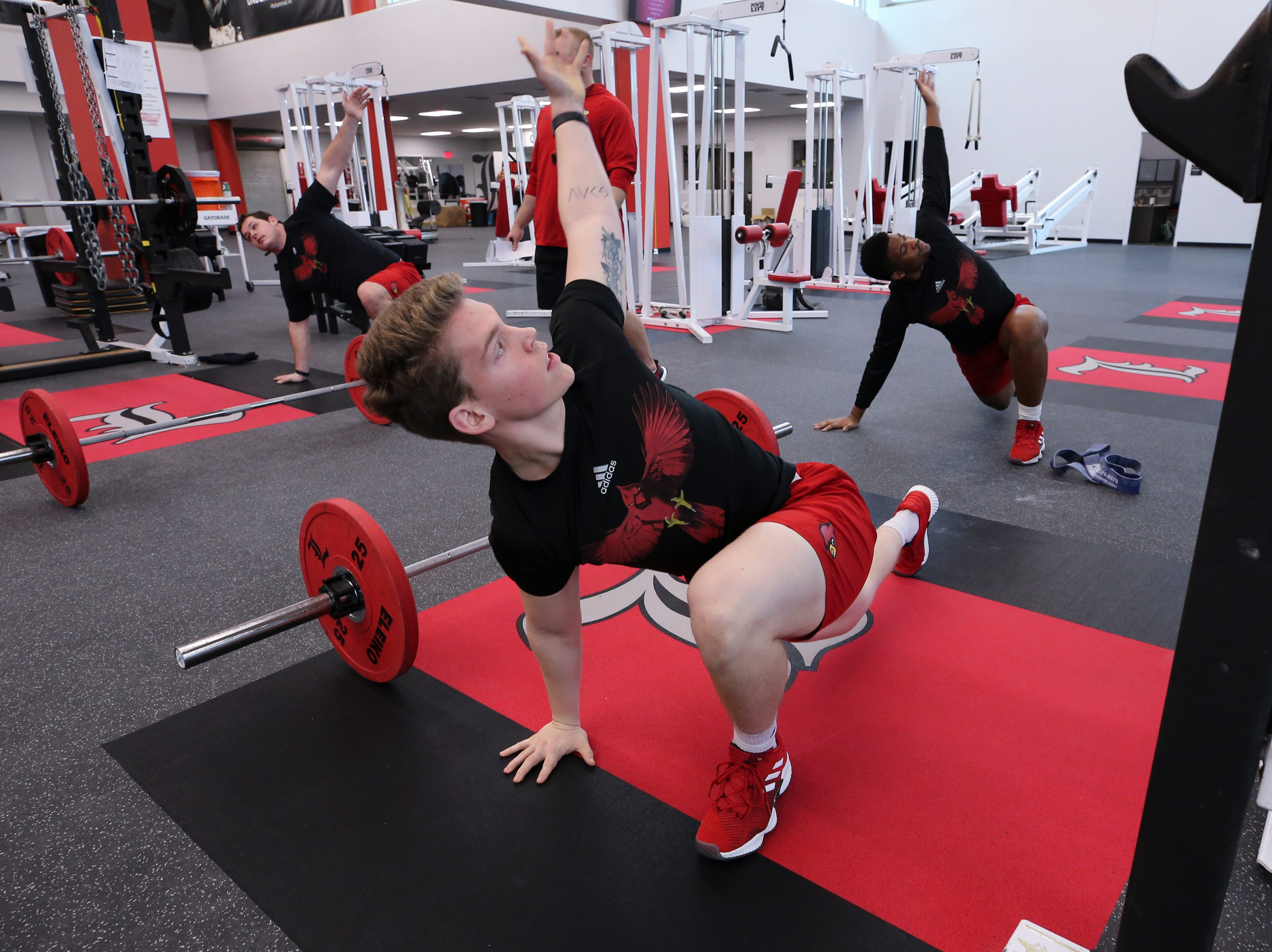 U of L long snapper Mitch Hall stretches before strength and conditioning at the Schnellenberger Complex.