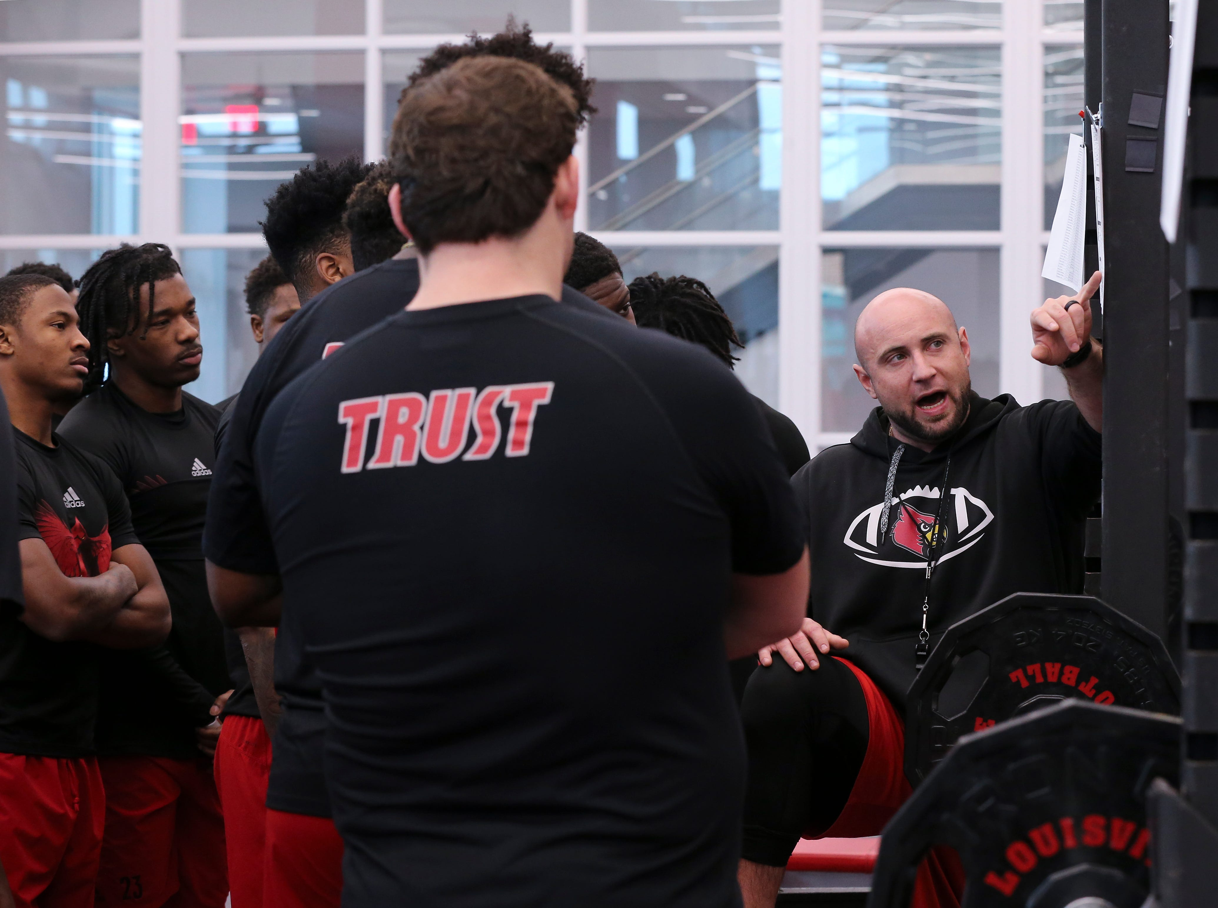 U of L strength coach Mike Sirignano, right, explains the day's schedule just before the team workout at Schnellenberger Complex.