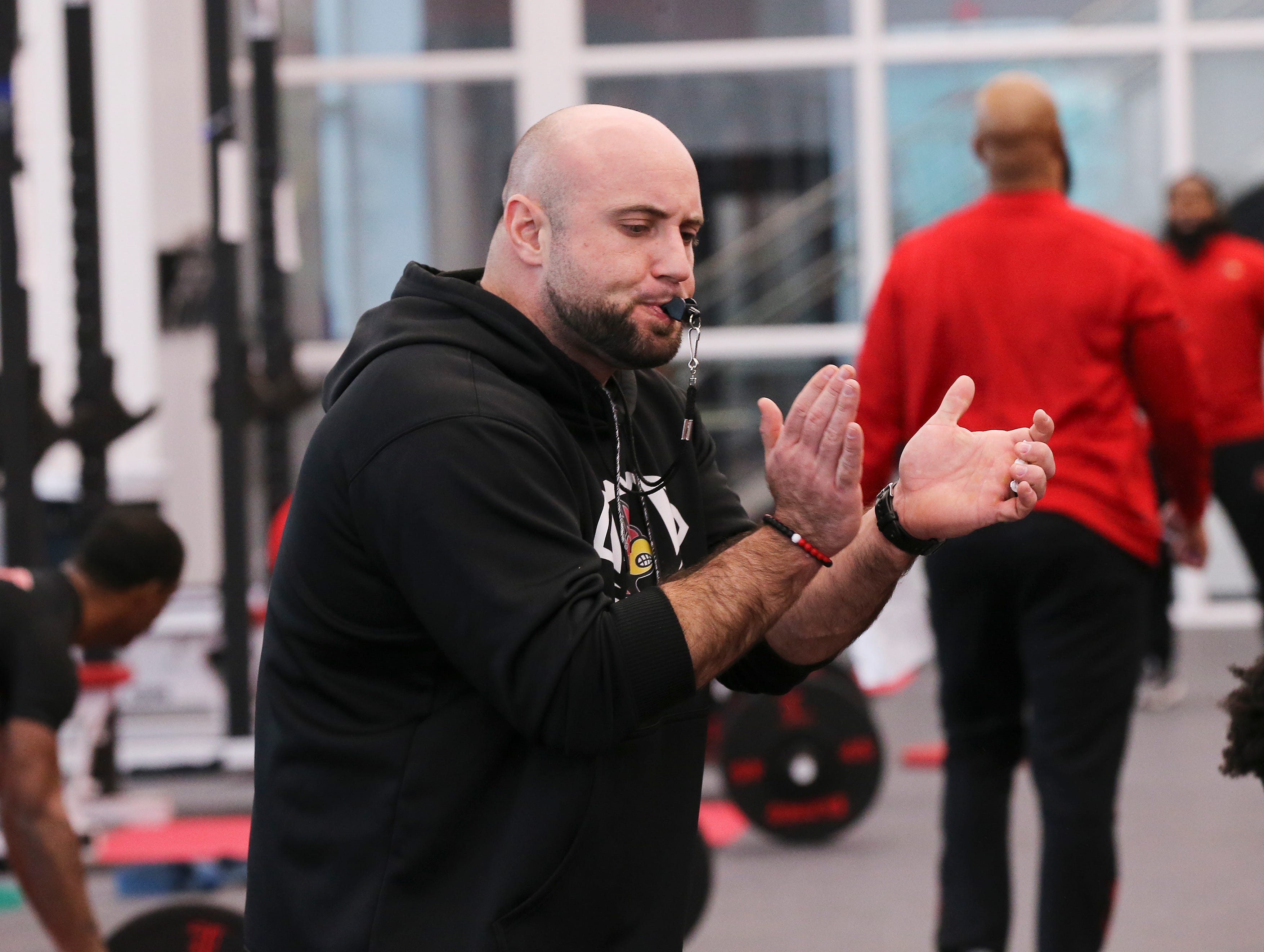 U of L strength coach Mike Sirignano encourages the team during a strength and conditioning workout at the Schnellenberger Complex.