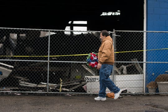 "Victor Ruiz of Lansing brings a wreath to hang on the security fence outside of the Eastside Gateway Monday afternoon, Feb. 4, 2019, to honor his brother-in-law John Bolan, who died Sunday morning from a fire at the small business incubator.  ""As soon as we heard about the fire, my wife (Katherine) and I raced over here to check on him, but he was already gone.   He had his entire future ahead of him,"" Ruiz said."