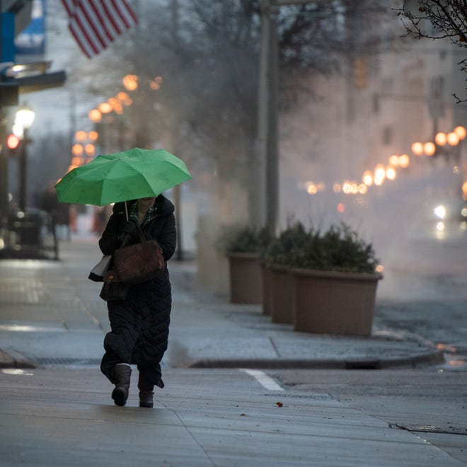 A woman walks in the rain along Capitol Ave. Monday evening, Feb. 4, 2019.
