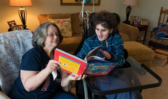 Home health-care worker Doreen Bowerman reads to 23-year-old Madeleine Mulder of Grand Ledge on Jan. 23, 2019.   Bowerman visits Madeleine two hours a day five days a week.