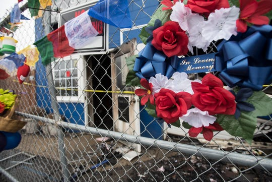 Balloons, Tibetan prayer flags, wreaths, and flowers adorn the fence outside of Lansing Eastside Gateway, where a fatal fire took place Sunday near the intersection of E. Kalamazoo and Larch St. in downtown Lansing.