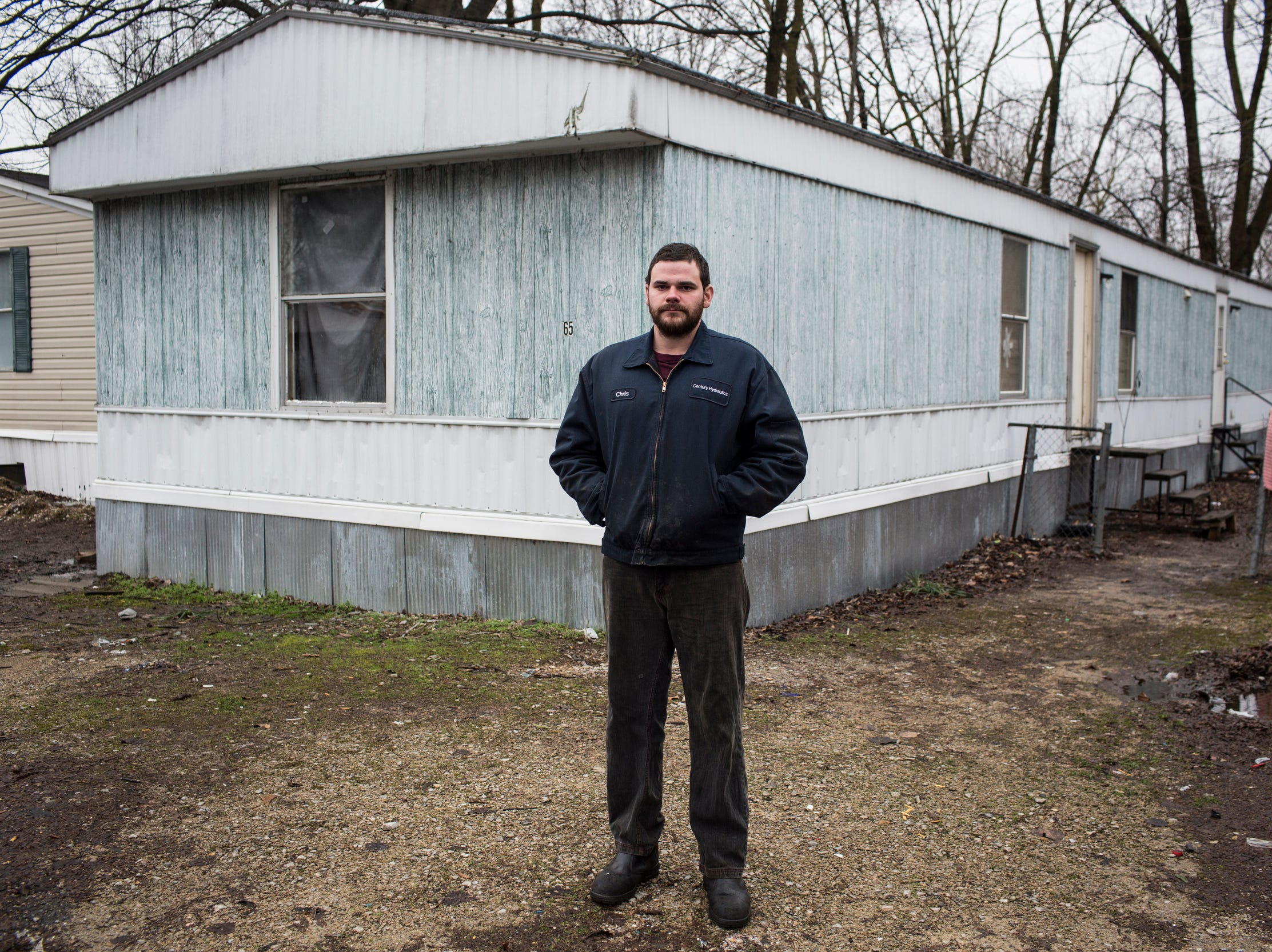 "January 23, 2019 - Chris Meyer stands outside of where he used to live with his girlfriend and son inside of Lakeshore. ""It was visible in the backyard, with the toilet paper floating around in the yard and the feces,"" he said. ""Every time you open the door you gotta smell it. Mosquitoes were terrible."""