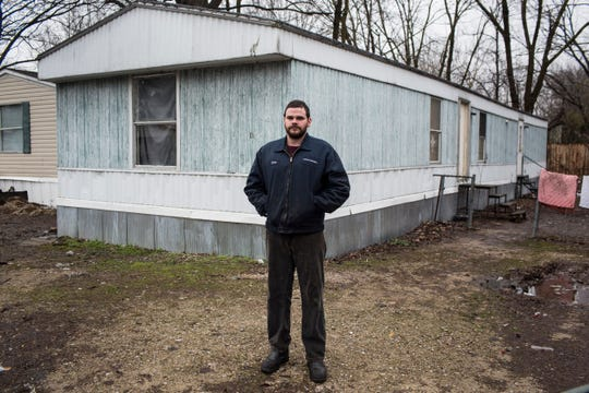 "Chris Meyer stands outside of where he used to live with his girlfriend and son inside of Lakeshore. ""It was visible in the backyard, with the toilet paper floating around in the yard and the feces,"" he said of the sewage that flowed through residents' yards. ""Every time you open the door you gotta smell it. Mosquitoes were terrible."""