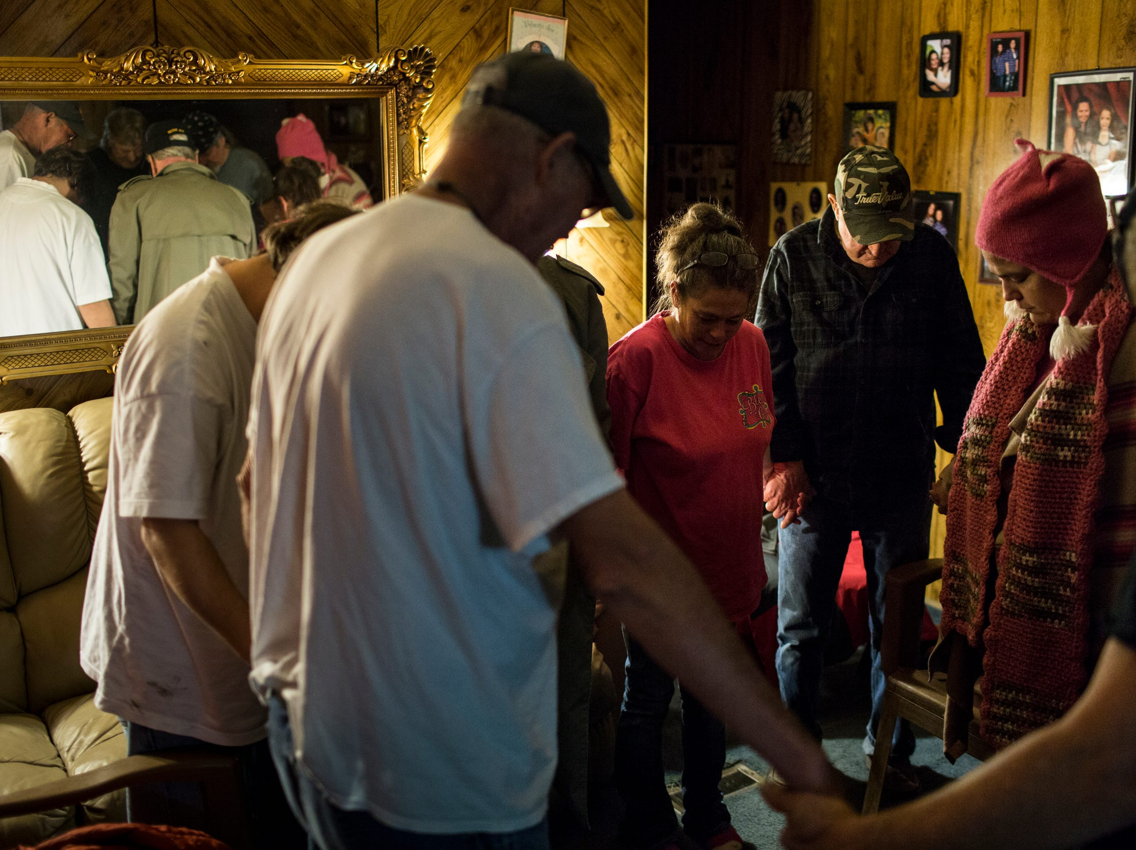 """January 24, 2019 - Members of the Lakeshore Community Improvement Group gather together for a prayer before the start of their meeting. The group meets every Thursday to discuss their community and talk about solutions for issues they see around their neighborhood. """"We're in this sinking Titanic together,"""" said co-chair Cassandra Meyer, who added that she thinks the group can help resolve other infrastructure issues in the neighborhood, such as tensions she says arise over parties and related traffic and noise complaints."""