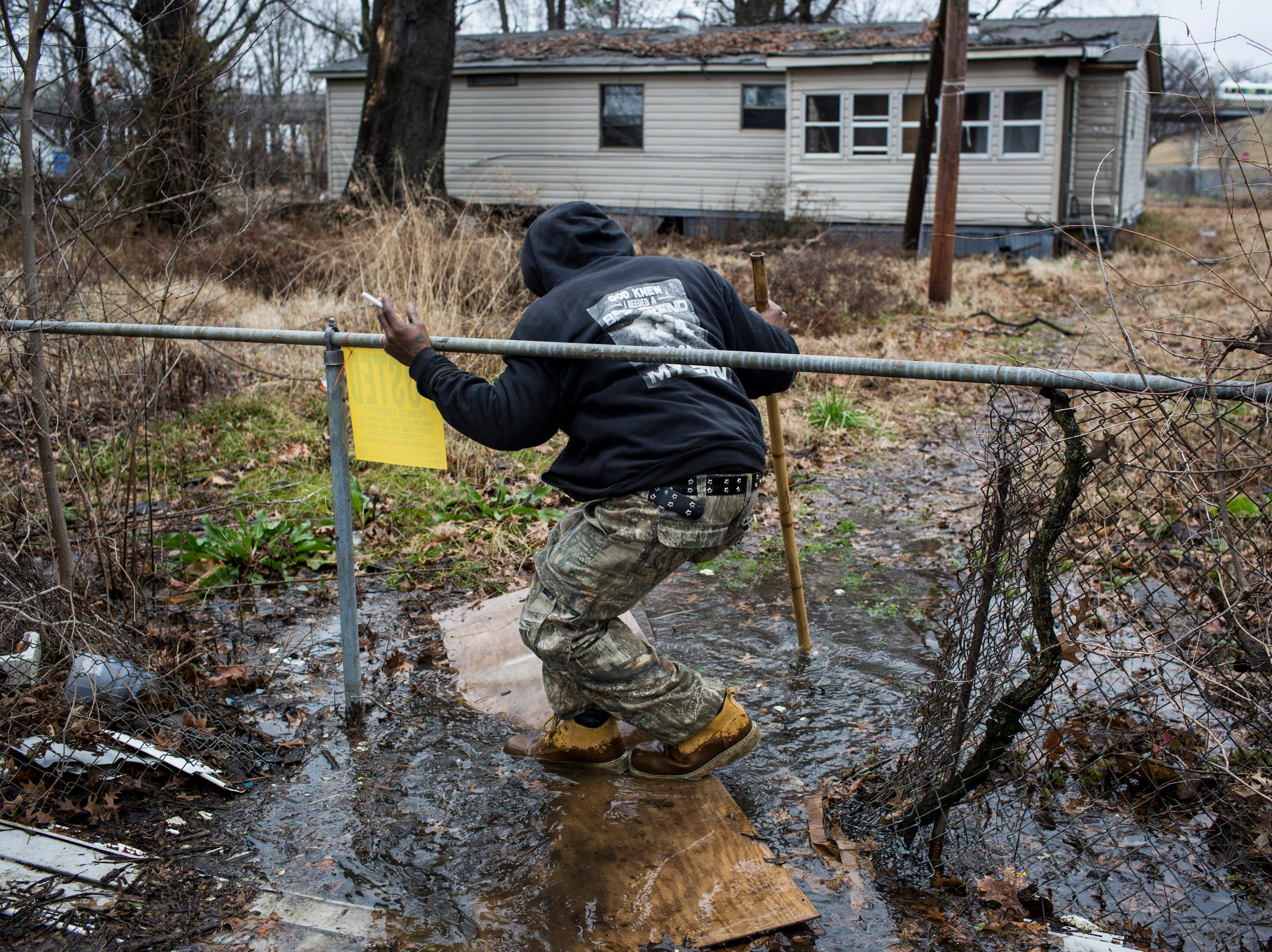 January 23, 2019 - Marcus Moore, a resident of Lakeshore in Marion, Arkansas, traverses a discarded door as he heads towards a friend's home. The Arkansas Department of Environmental Quality records show that Lakeshore's approximately 3-mile sewage system has a long history of issues with stormwater inflow and sewage overflows.
