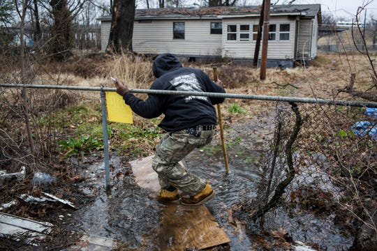 Marcus Moore, a resident of Lakeshore in Marion, Arkansas, traverses a discarded door as he heads towards a friend's home. The Arkansas Department of Environmental Quality records show that Lakeshore's approximately 3-mile sewage system has a long history of issues with stormwater inflow and sewage overflows.