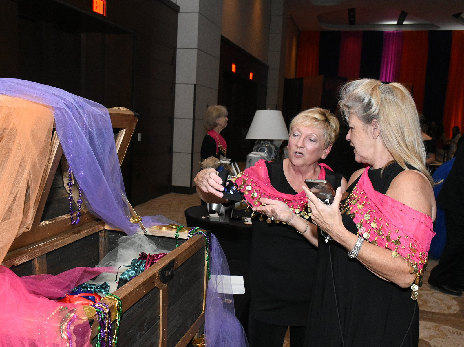 Kathi Swaja, left, and Shelley Slechta inspect the two carat diamond earrings from Kathein Jewelers of Marco. The Marco Island unit of the American Cancer Society held the Imagination Ball Friday evening at the JW Marriott hotel, raising funds to continue the fight against cancer.