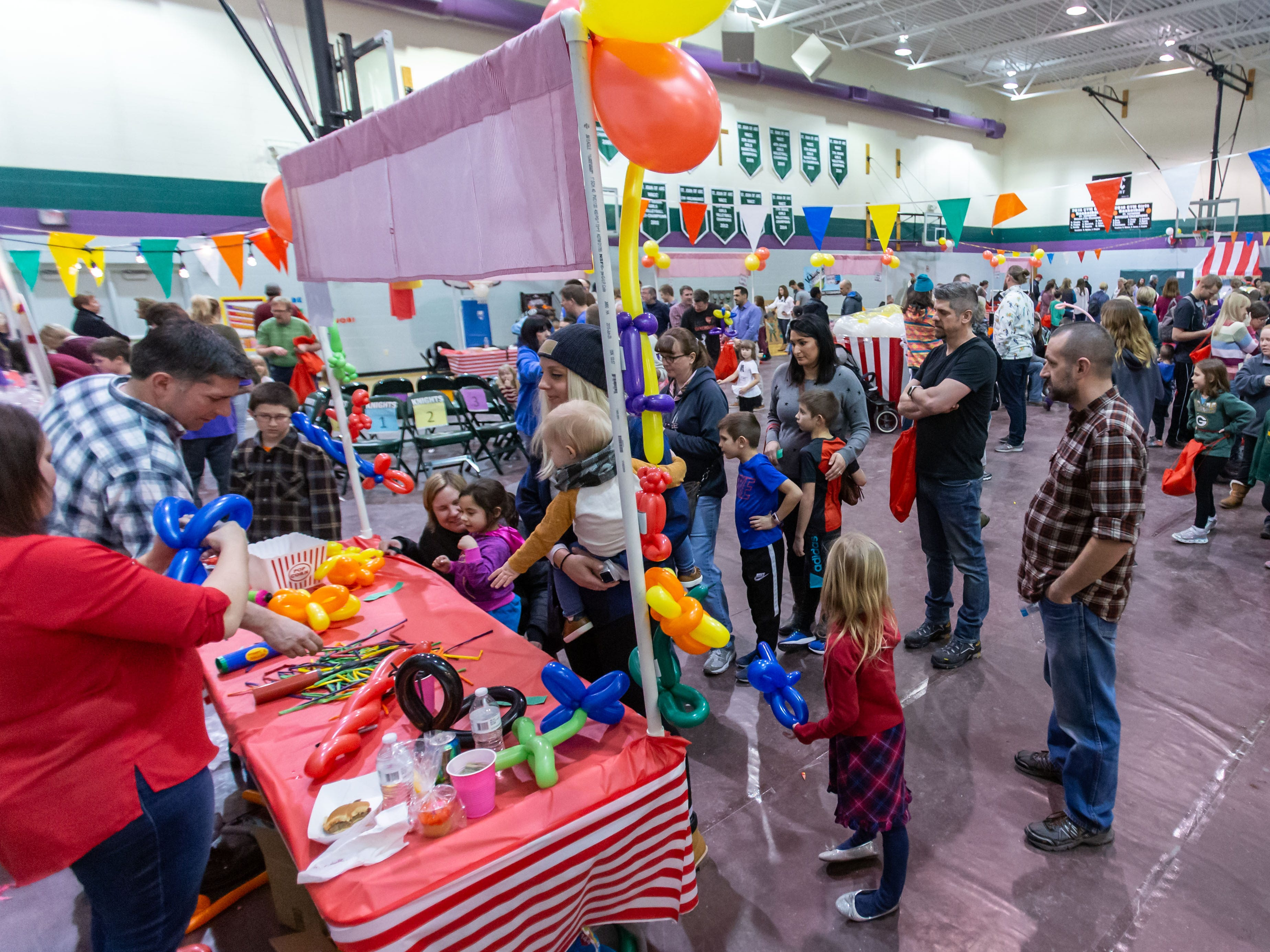 Youngsters gather round the balloon table for a custom creation during the 9th annual St. Joan of Arc Carnival in Nashotah on Friday, Feb. 1, 2019. The family-friendly event features carnival games, food, face painting, balloon animals, a fortune teller and more.