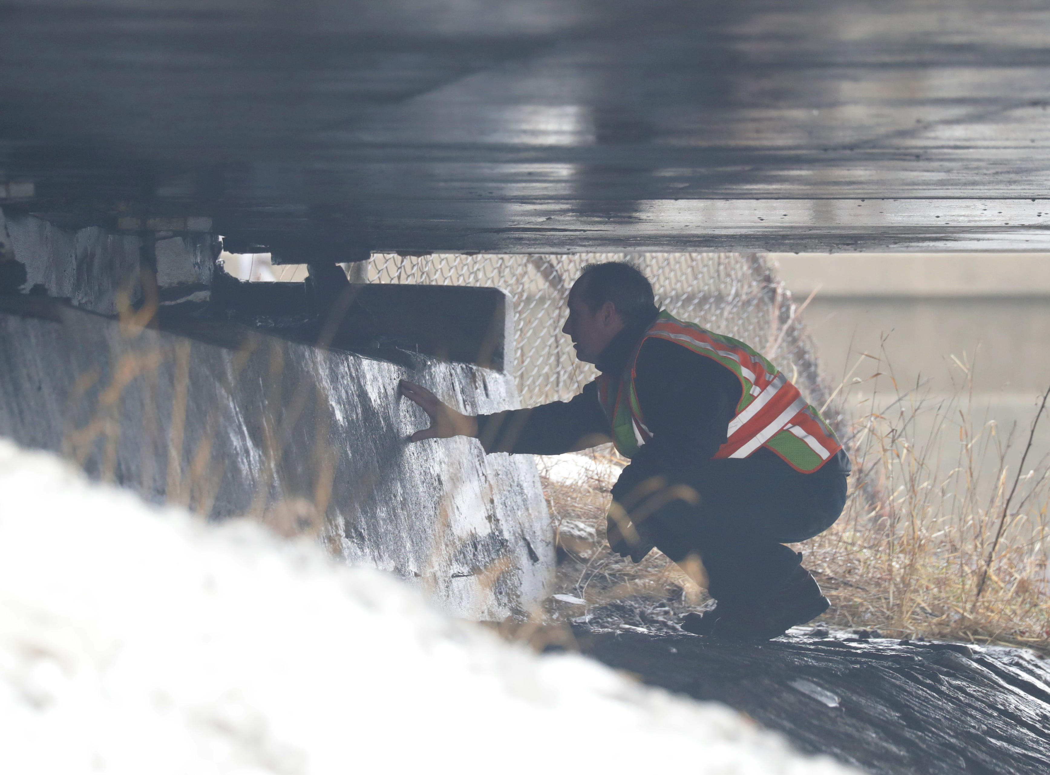 A Wisconsin Department of Transportation official inspects the bridge as a semi truck is stuck.
