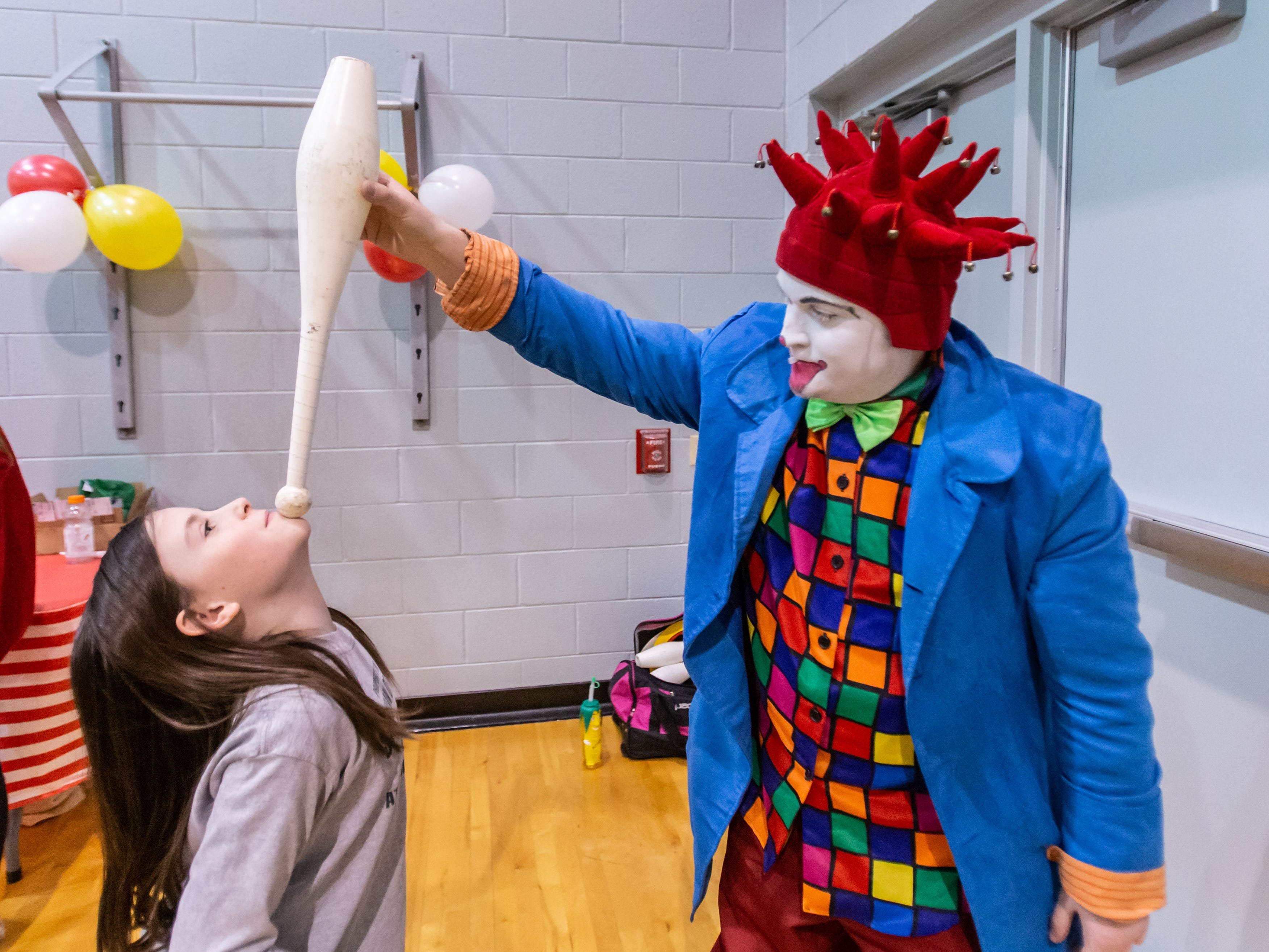 Jason Beaumont of West Allis teaches Molly Flint, 9, of Oconomowoc how to balance a juggler's pin during the 9th annual St. Joan of Arc Carnival in Nashotah on Friday, Feb. 1, 2019. The family-friendly event features carnival games, food, face painting, balloon animals, a fortune teller and more.