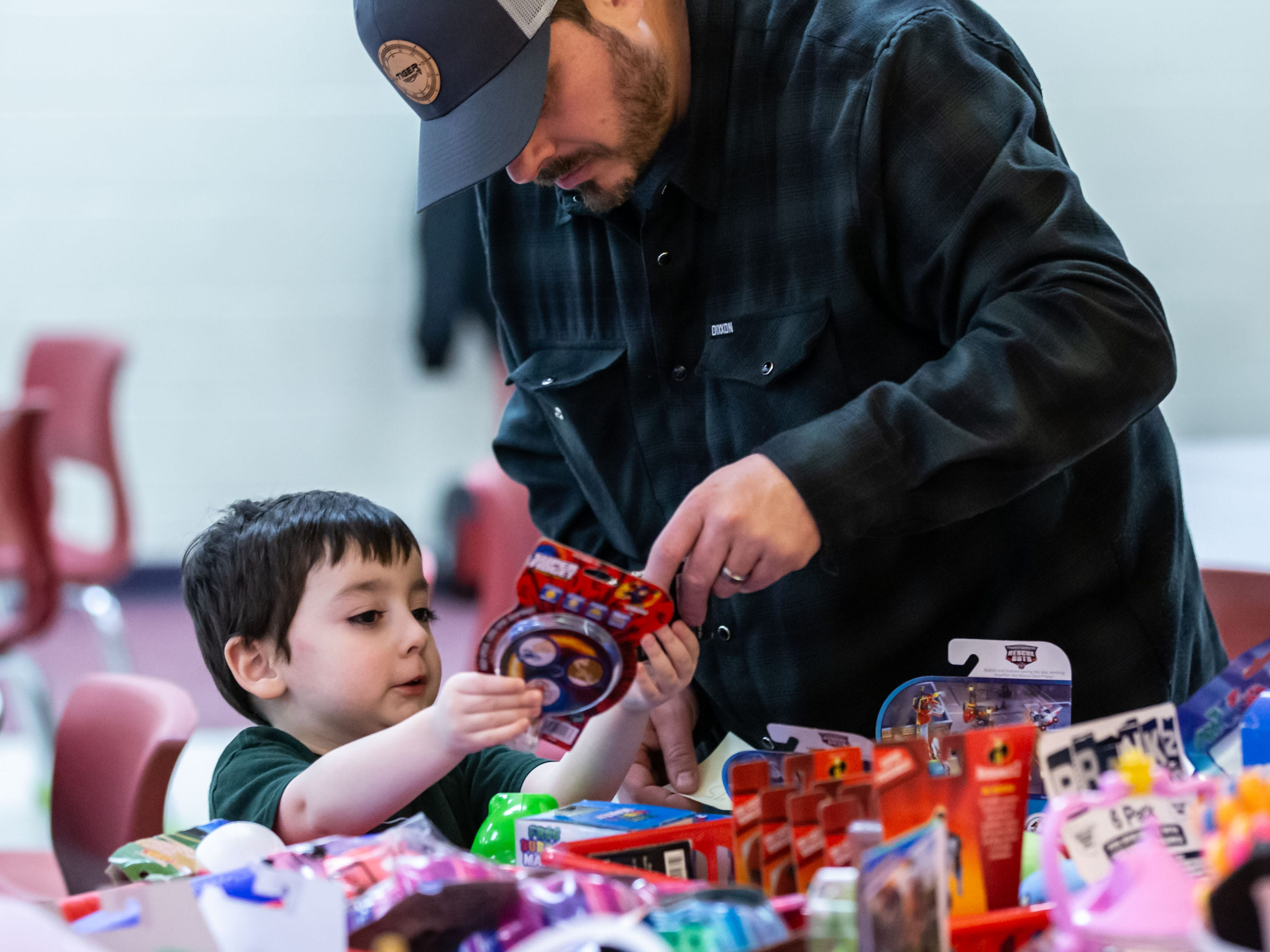 Four-year-old Abel Dettmann of Oconomowoc selects a prize with a little help from his father Dan during the 9th annual St. Joan of Arc Carnival in Nashotah on Friday, Feb. 1, 2019. The family-friendly event features carnival games, food, face painting, balloon animals, a fortune teller and more.