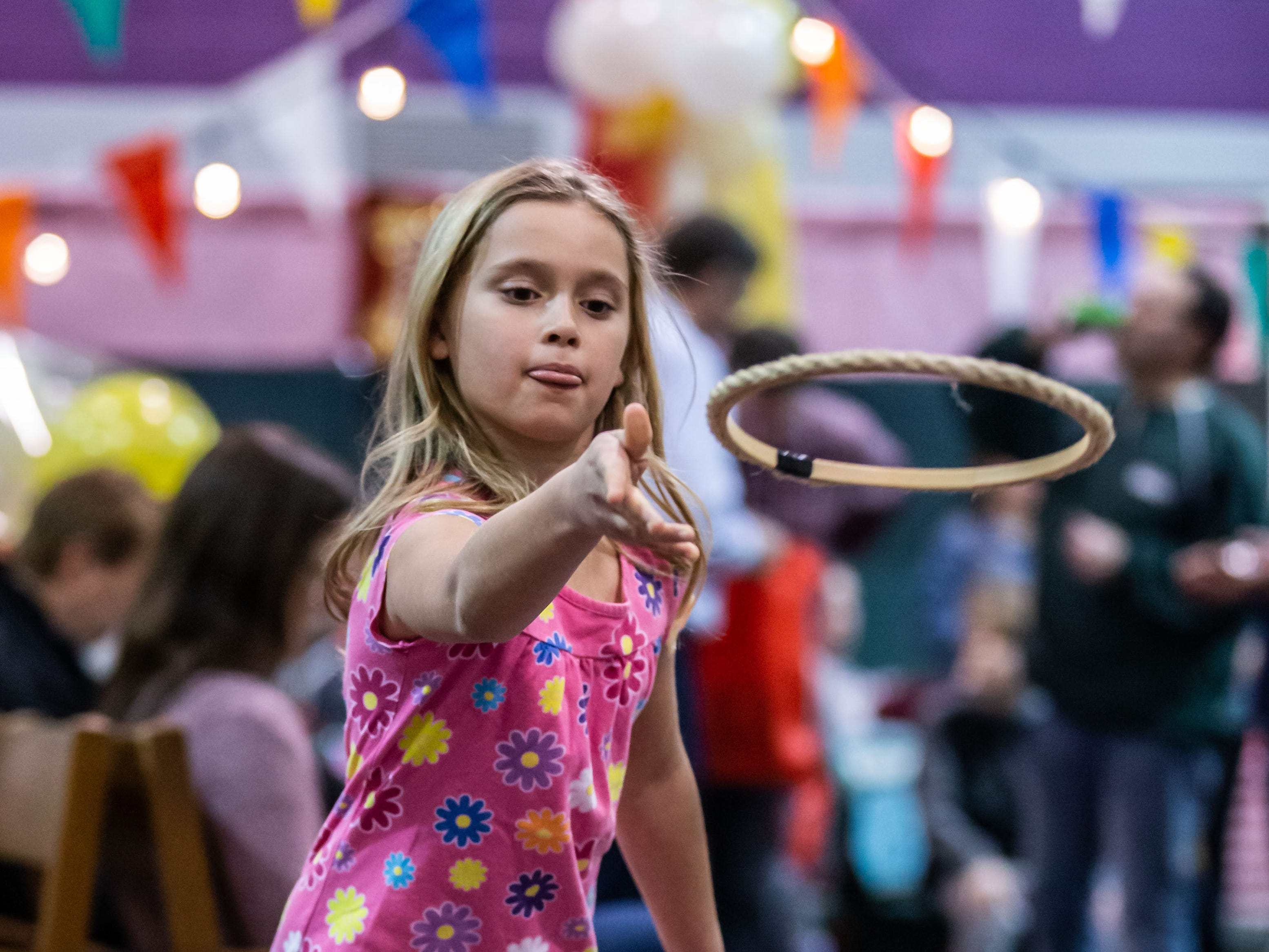 Gaby Bichanich, 7, of Oconomowoc, plays a hoop game during the 9th annual St. Joan of Arc Carnival in Nashotah on Friday, Feb. 1, 2019. The family-friendly event features carnival games, food, face painting, balloon animals, a fortune teller and more.