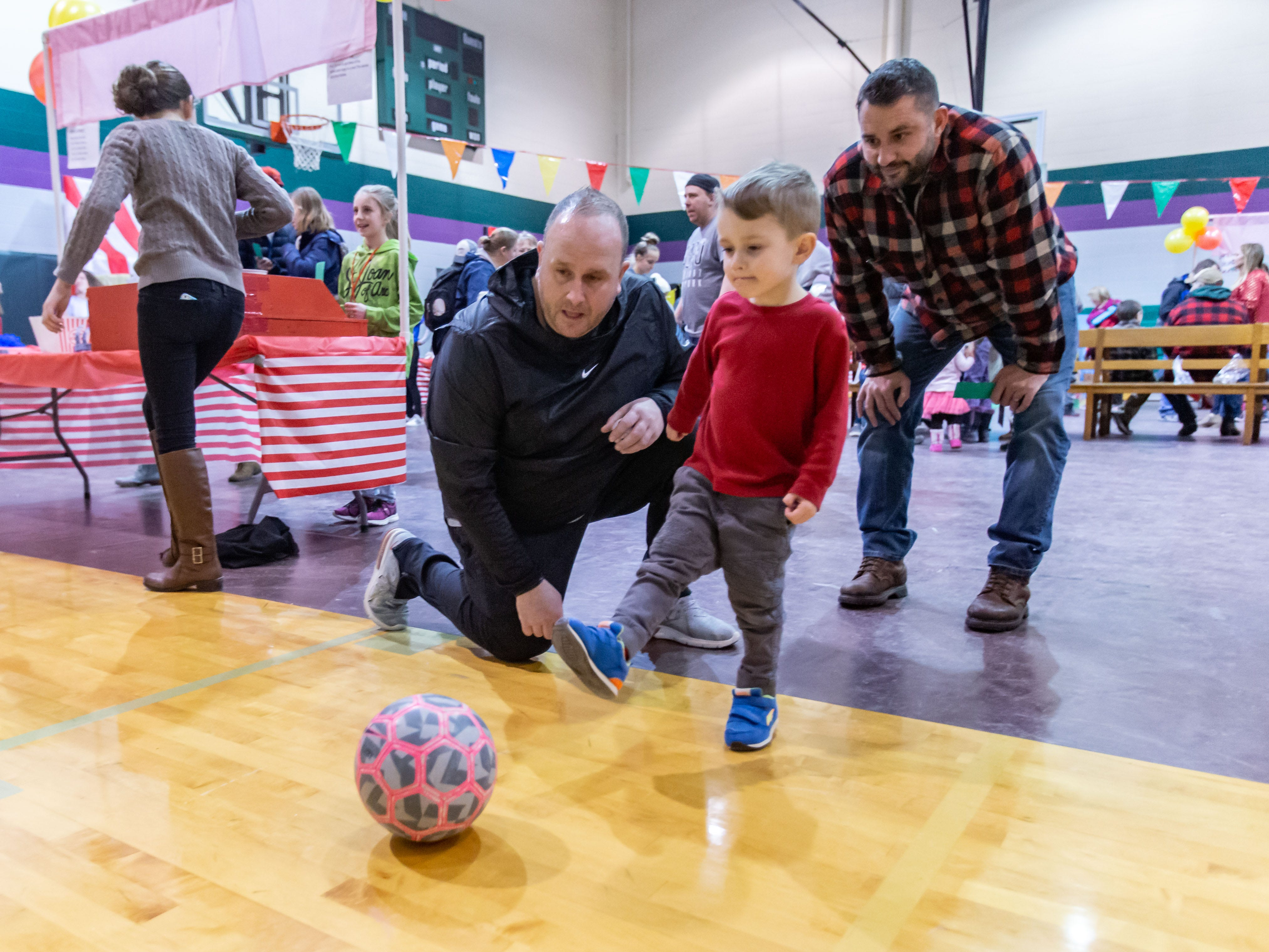 Scott Asher (left), Executive Director of Strike FC Wisconsin soccer club, gives pointers to three-year-old Beau Radke of Delafield as he tries a soccer game during the 9th annual St. Joan of Arc Carnival in Nashotah on Friday, Feb. 1, 2019. The family-friendly event features carnival games, food, face painting, balloon animals, a fortune teller and more.