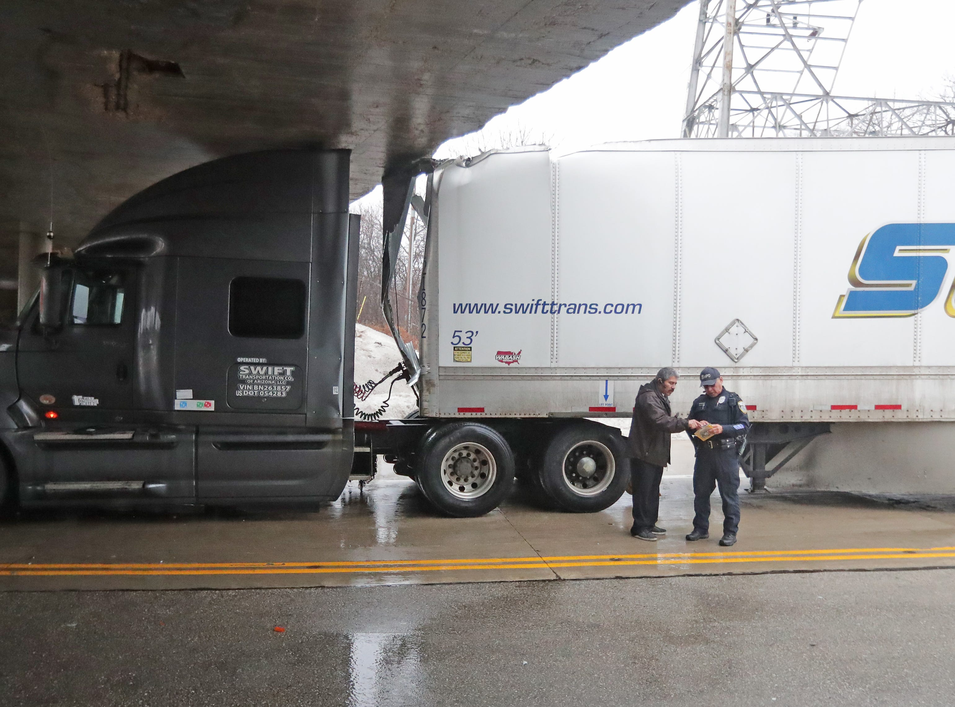 A truck driver talks to a Milwaukee Police officer as his semi truck is stuck.