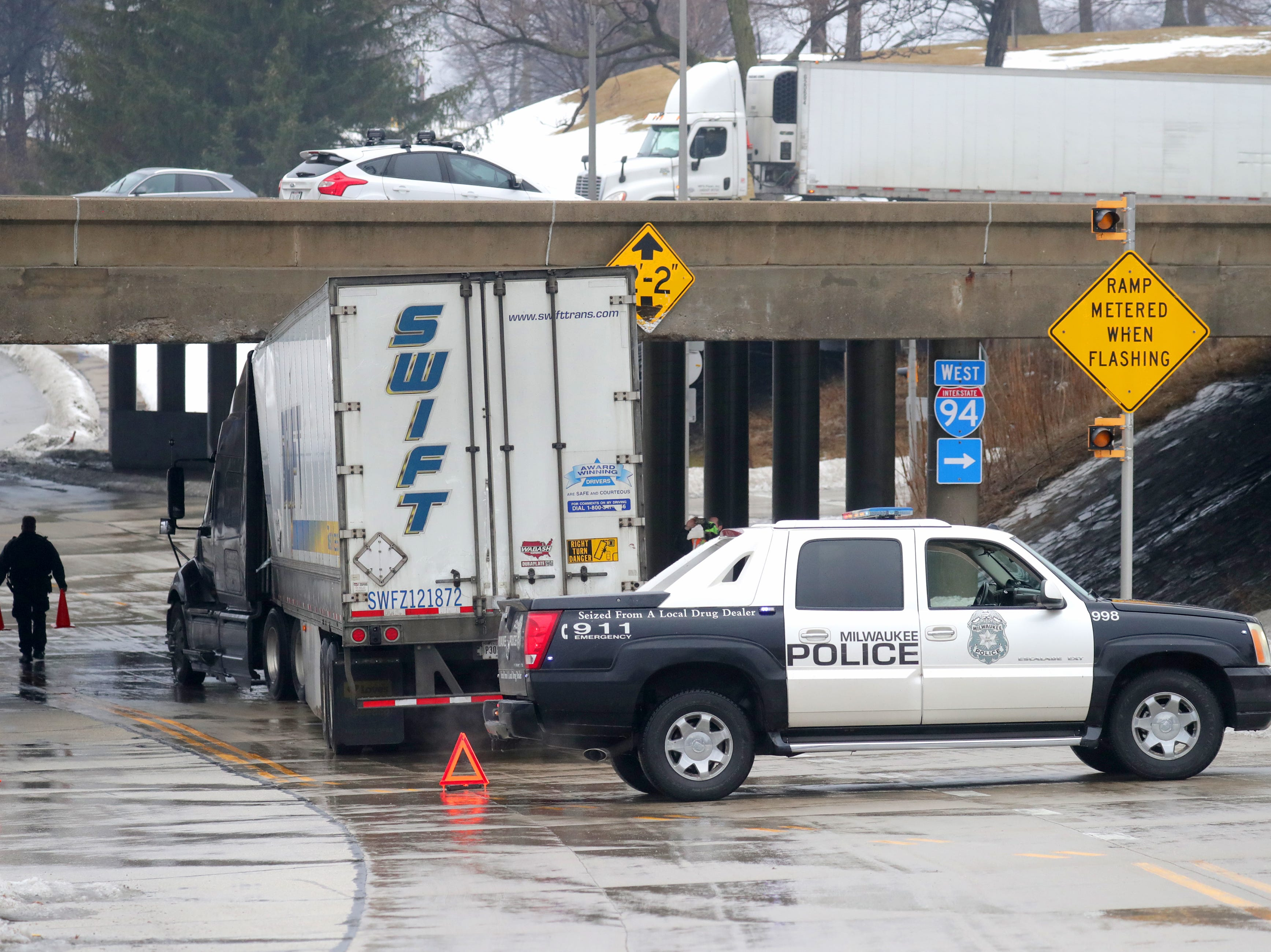 Milwaukee Police place cones around the site where the semi truck is stuck.