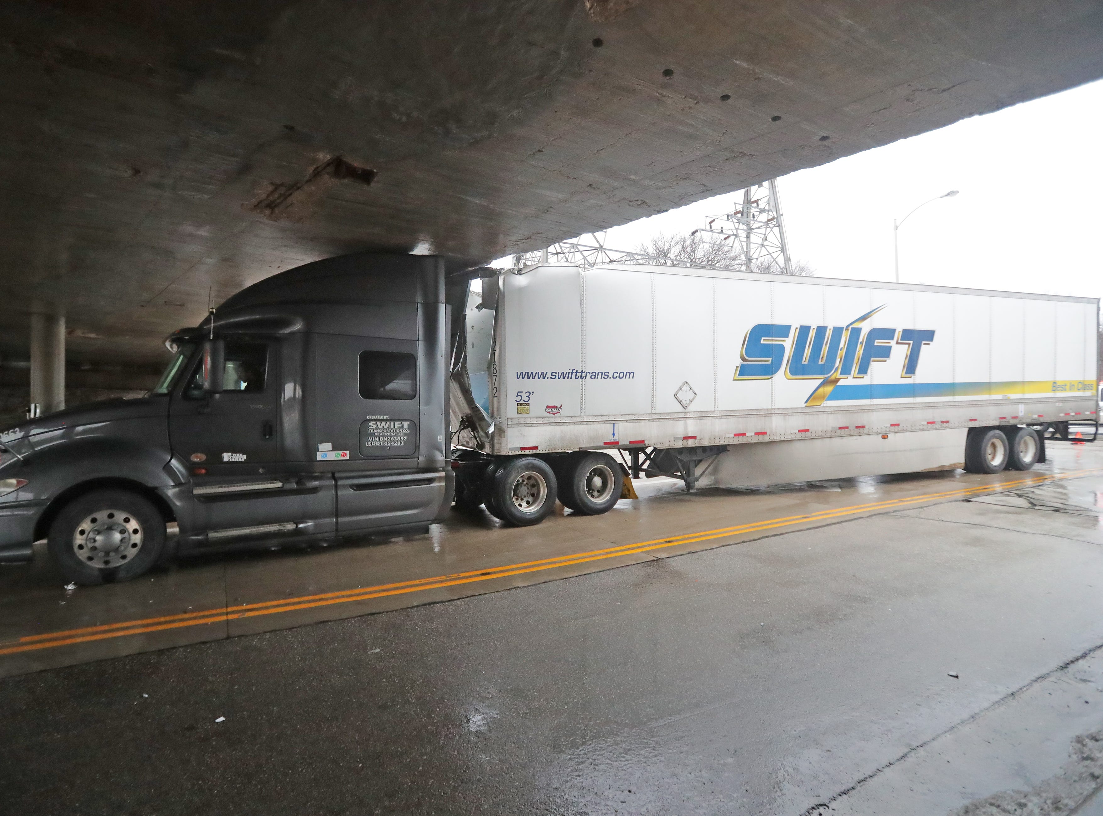 A semi truck is stuck under the I-94 bridge on General Mitchell Boulevard in Milwaukee on Monday.