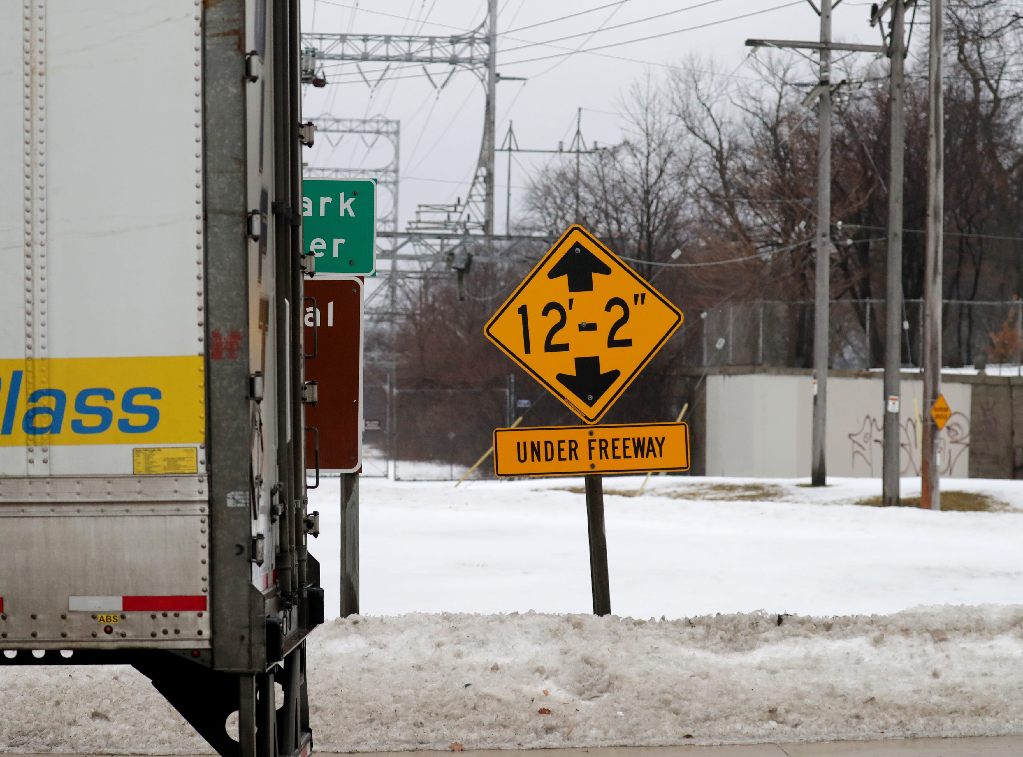 A sign marking the clearance of the bridge is seen as the semi truck is stuck.