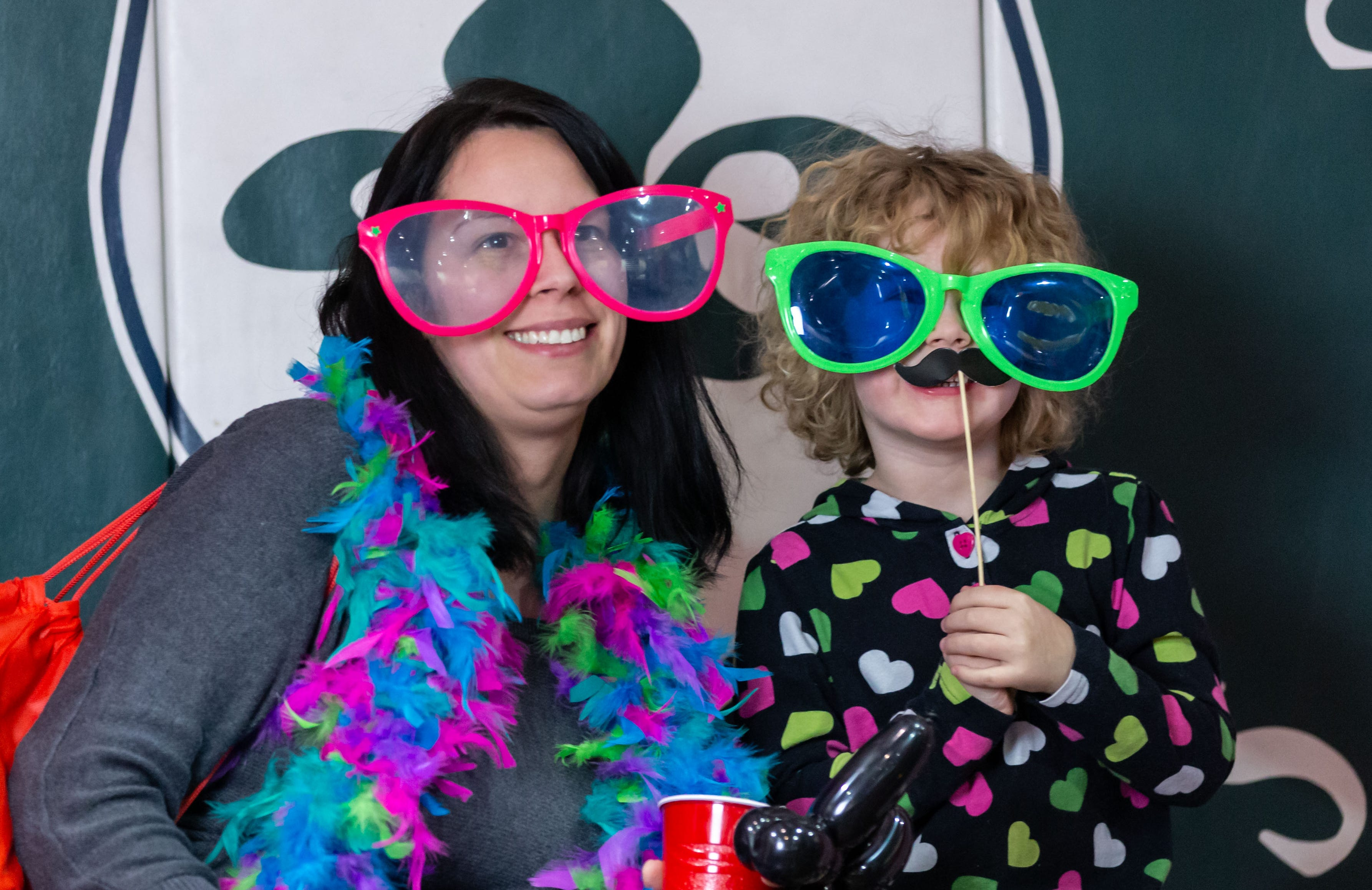 Sarah Paulson of Oconomowoc and her daughter Ava, 5, take a seat in the photo booth during the 9th annual St. Joan of Arc Carnival in Nashotah on Friday, Feb. 1, 2019. The family-friendly event features carnival games, food, face painting, balloon animals, a fortune teller and more.