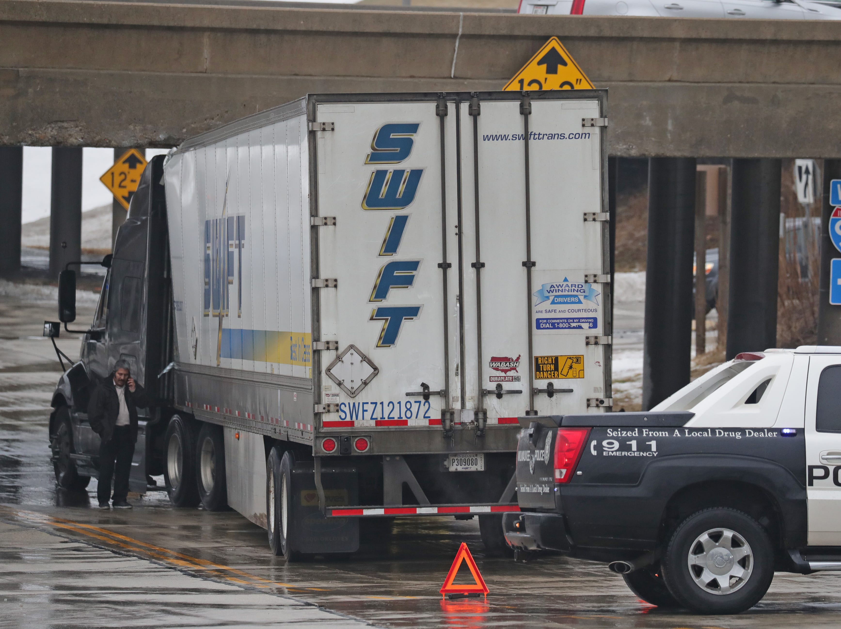 A truck driver talks on his phone as his semi truck is stuck under the I-94 bridge on General Mitchell Boulevard in Milwaukee on Monday. The trailer was empty. It's the second truck to be stuck in the last three weeks as a truck full of Pabst Blue Ribbon beer was lodged under bridge just last month on January 15.