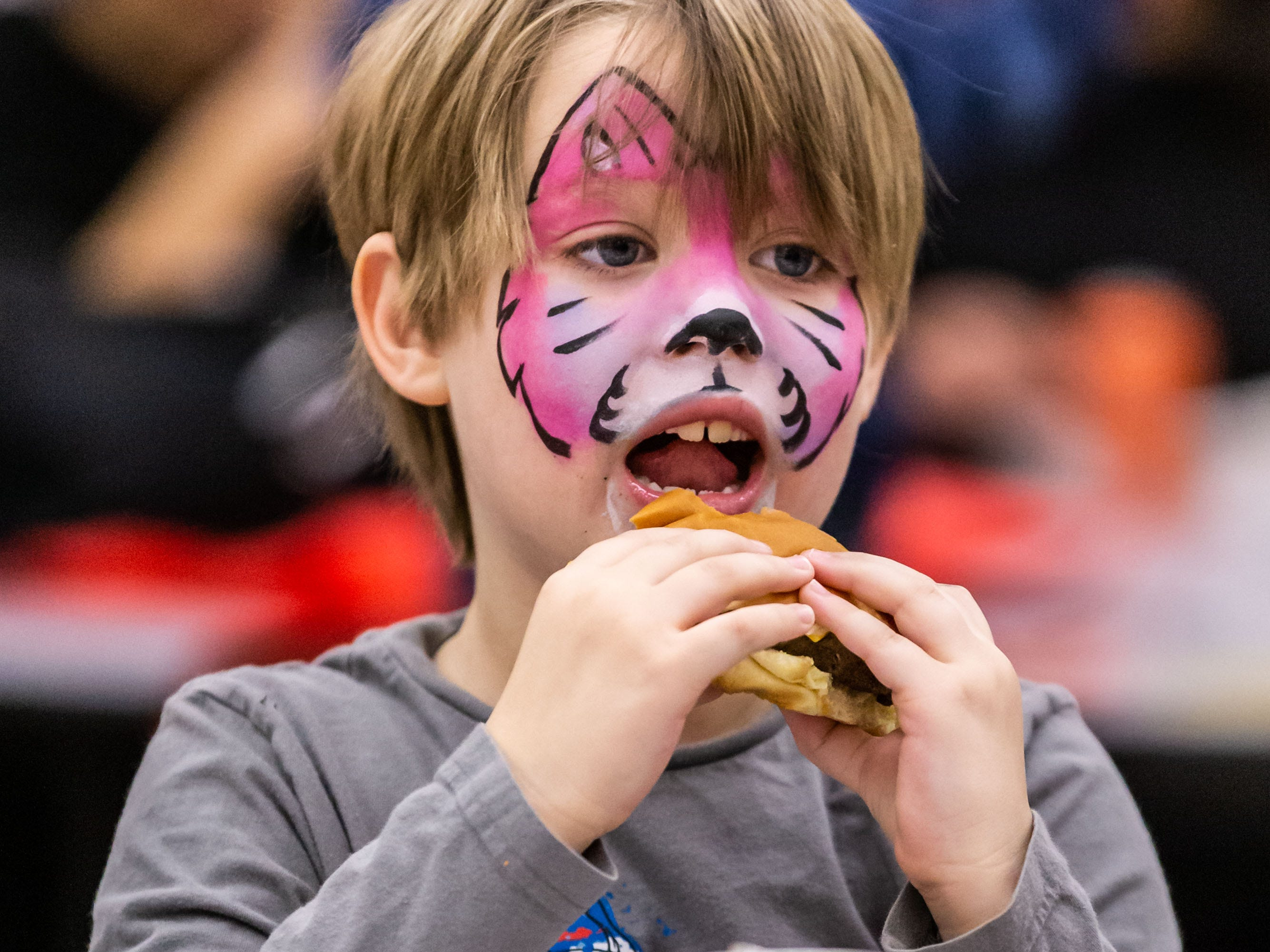 Luke Krieser, 8, of Oconomowoc, enjoys a hamburger during the 9th annual St. Joan of Arc Carnival in Nashotah on Friday, Feb. 1, 2019. The family-friendly event features carnival games, food, face painting, balloon animals, a fortune teller and more.
