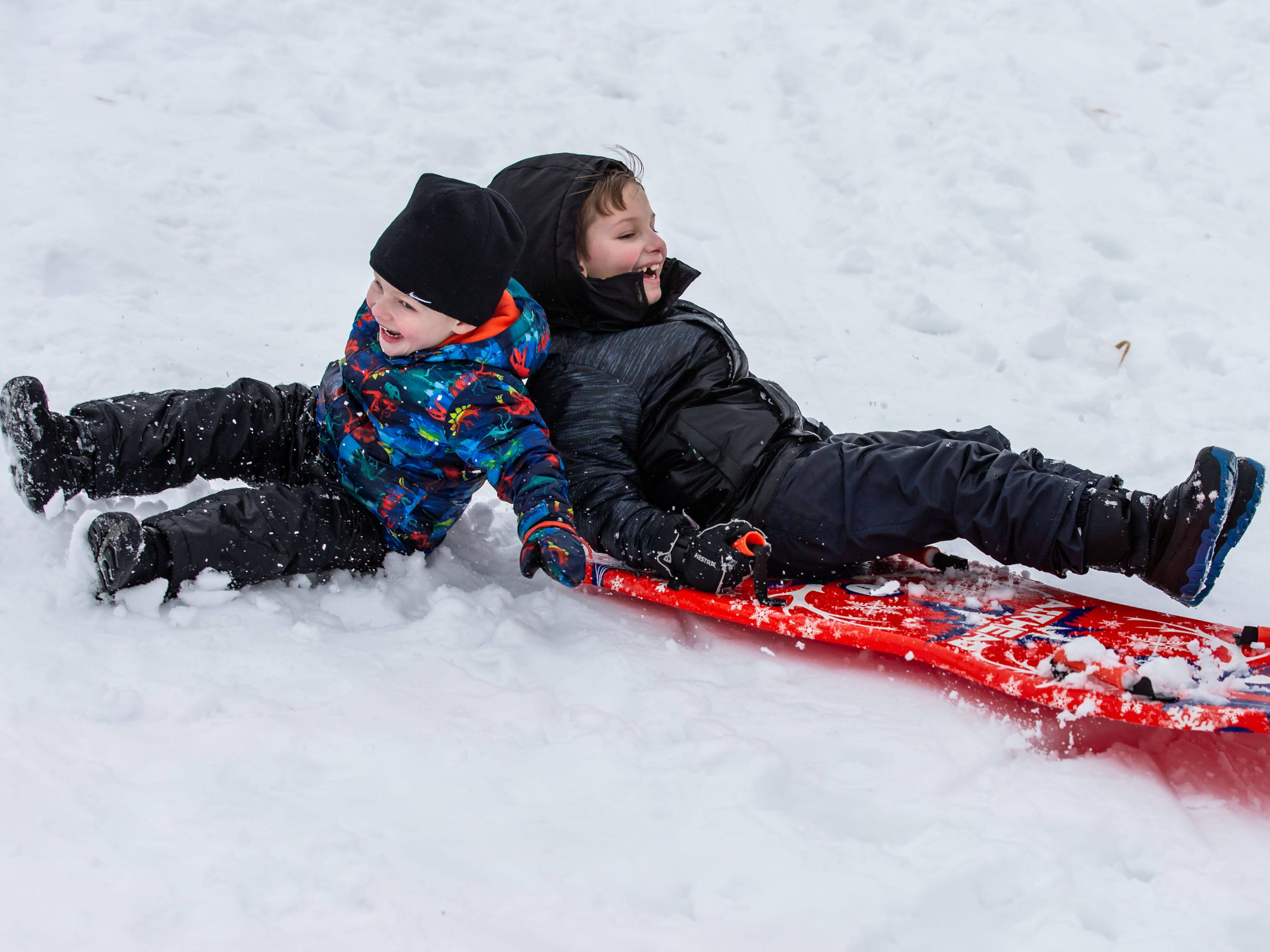 Three-year-old Silas Newsted (left) of Cedarburg and his brother Gavin, 8, take a tumble while sledding at Mee-Kwon Park in Mequon on Saturday, Feb. 2, 2019. The park is open 7 days a week from 6 a.m. to 9 p.m. but is not lighted.