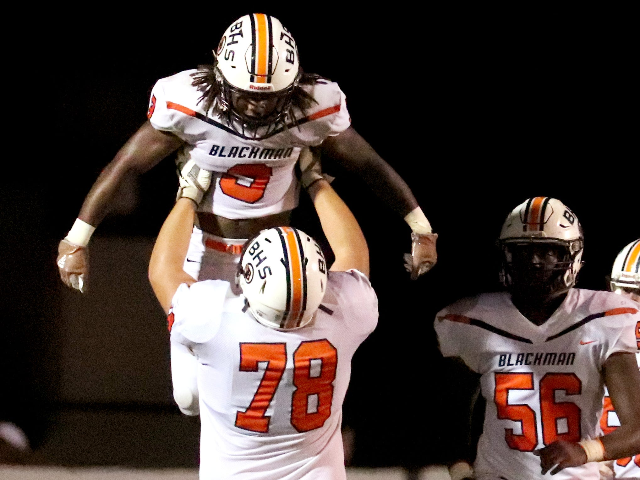 Blackman's Michael Arnal-Brown (78) lifts Tamicus Napier up in the air to celebrate Napier's touchdown against Smyrna during the game at Smyrna High School on Friday, Sept. 7, 2018.