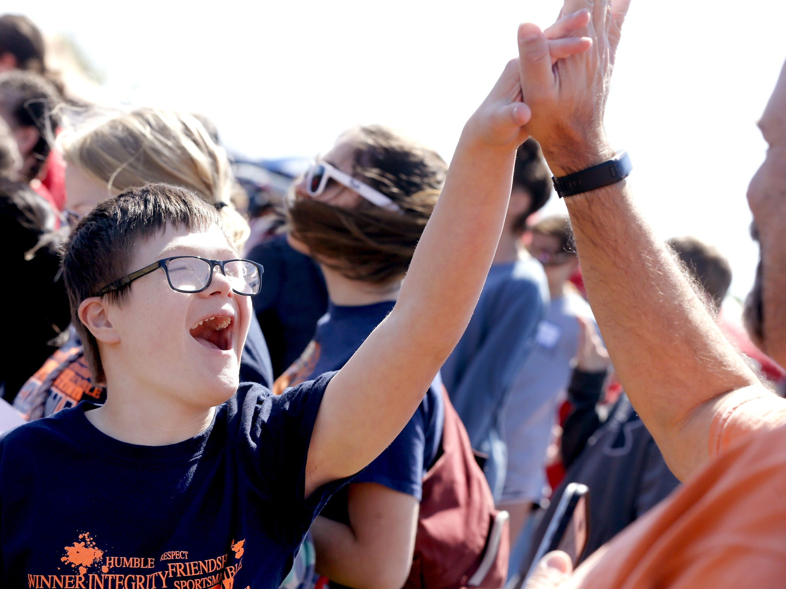 Patrick Shupp of Blackman Middle school gives his dad Bill Shupp several high-fives after running a race in the Area 16 Special Olympics featuring the Rutherford County and Murfreesboro City Schools along with other independent groups held Olympic Games at MTSU's soccer field and Track stadium on Friday, April 13, 2018.