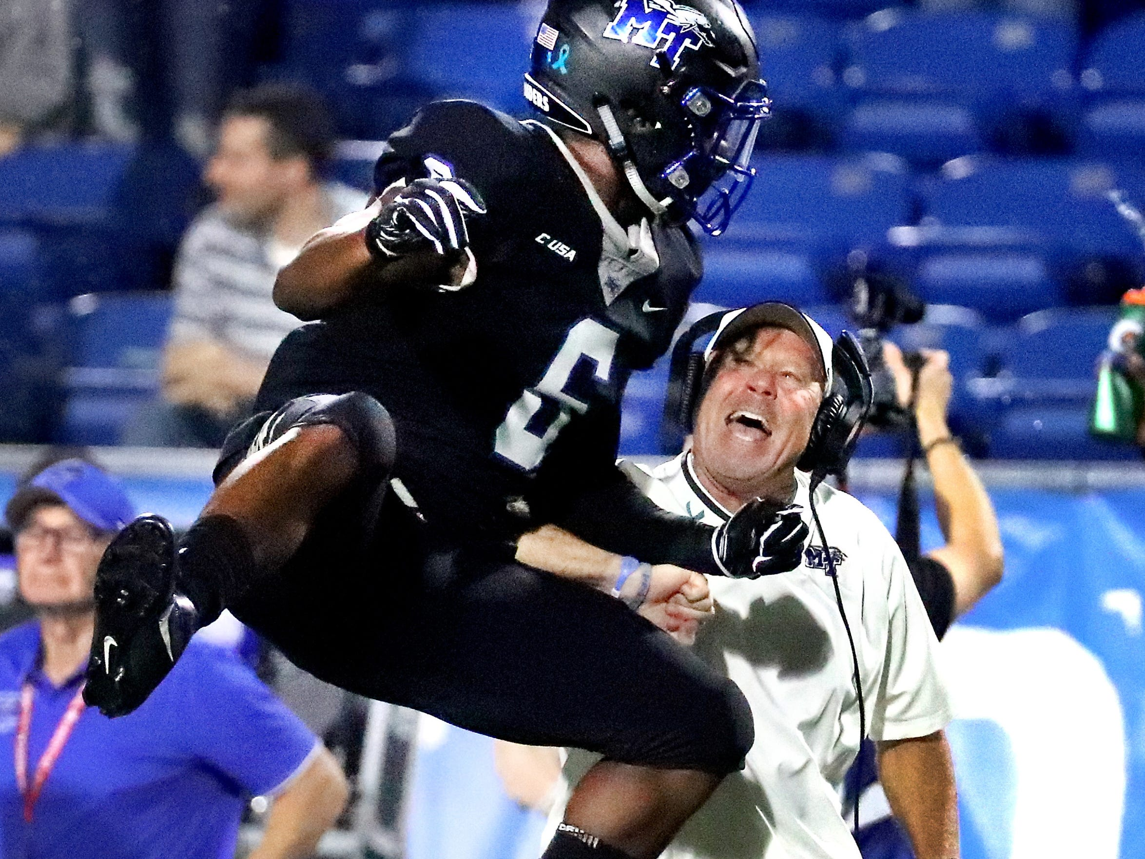 MTSU's head coach Rick Stockstill celebrates an interception against FAU made by Jovante Moffatt (7) with Khalil Brooks (6) on the sidelines in the final seconds of the game at MTSU, on Saturday, Sept. 29, 2018.