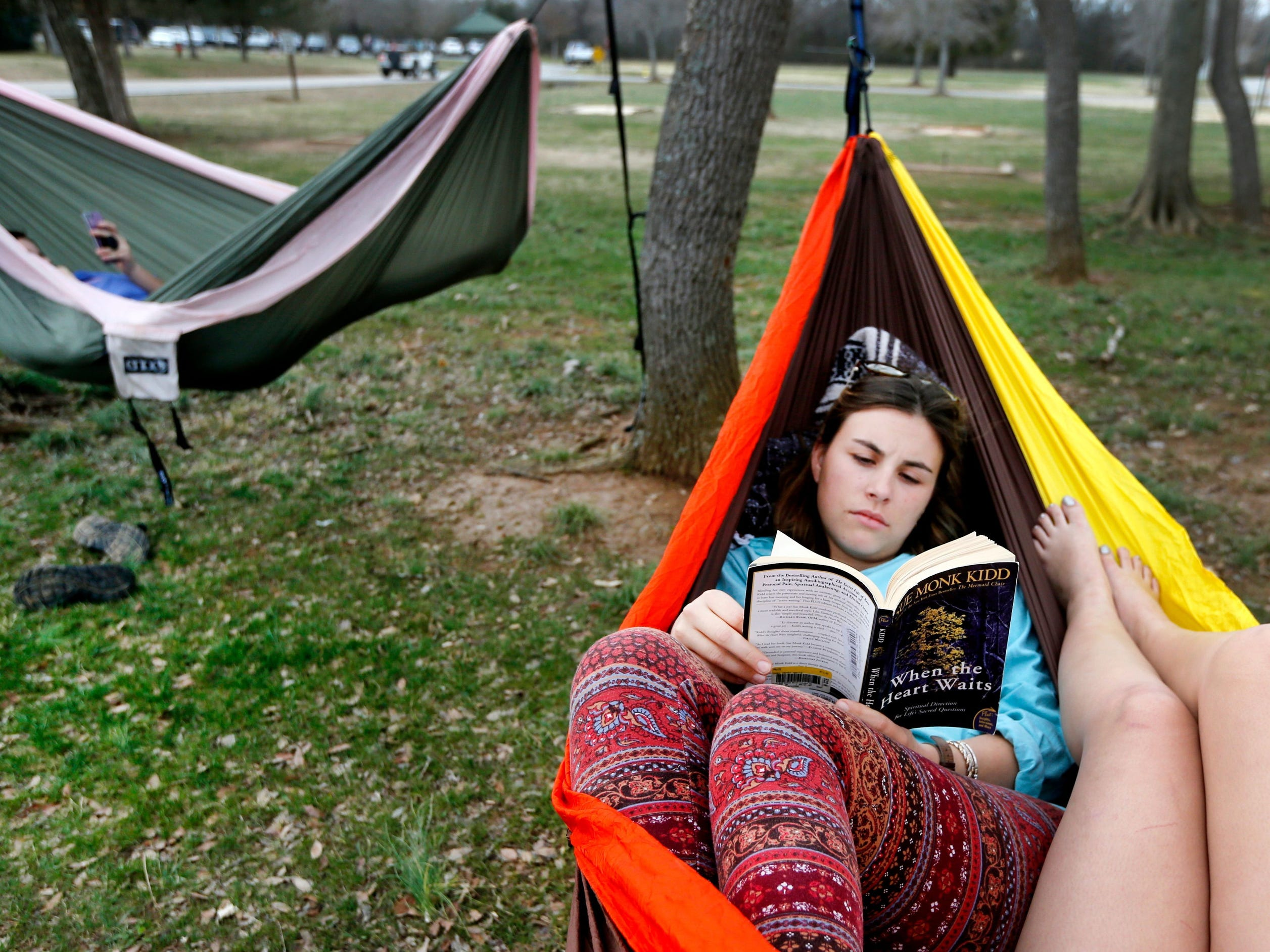 "Bethany Mohr, 23, reads ""When the Heart Waits"" by Sue Monk Kidd in a hammock with her sister Grace Dawson, 16, as her other sister Bella Dawson, 13 reads on her phone in another hammock in Barfield Crescent Park, in Murfreesboro, on Monday, Feb. 19, 2018. The 3 had a picnic in the park before lounging in hammocks enjoying the unusual warm weather."
