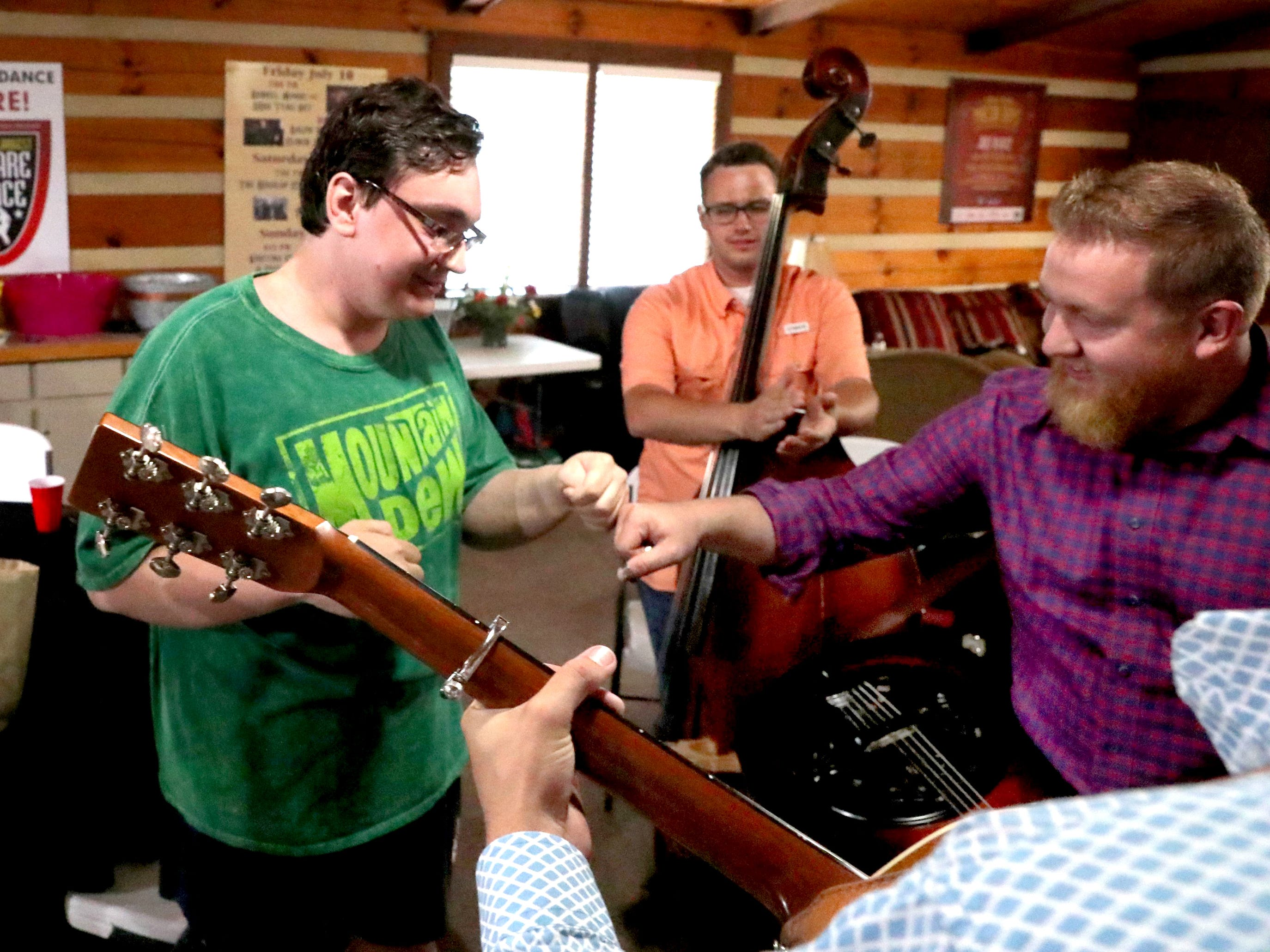 Kyle Nelson, who traveled from Grand Marais, in Northern Minnesota, to see his favorite band Flatt Lonesome, gets a fist bump from Buddy Robertson with Flatt Lonesome as he meets and sings with the band before they perform at the 41st annual Uncle Dave Macon Days Festival on Friday, July 13, 2018.