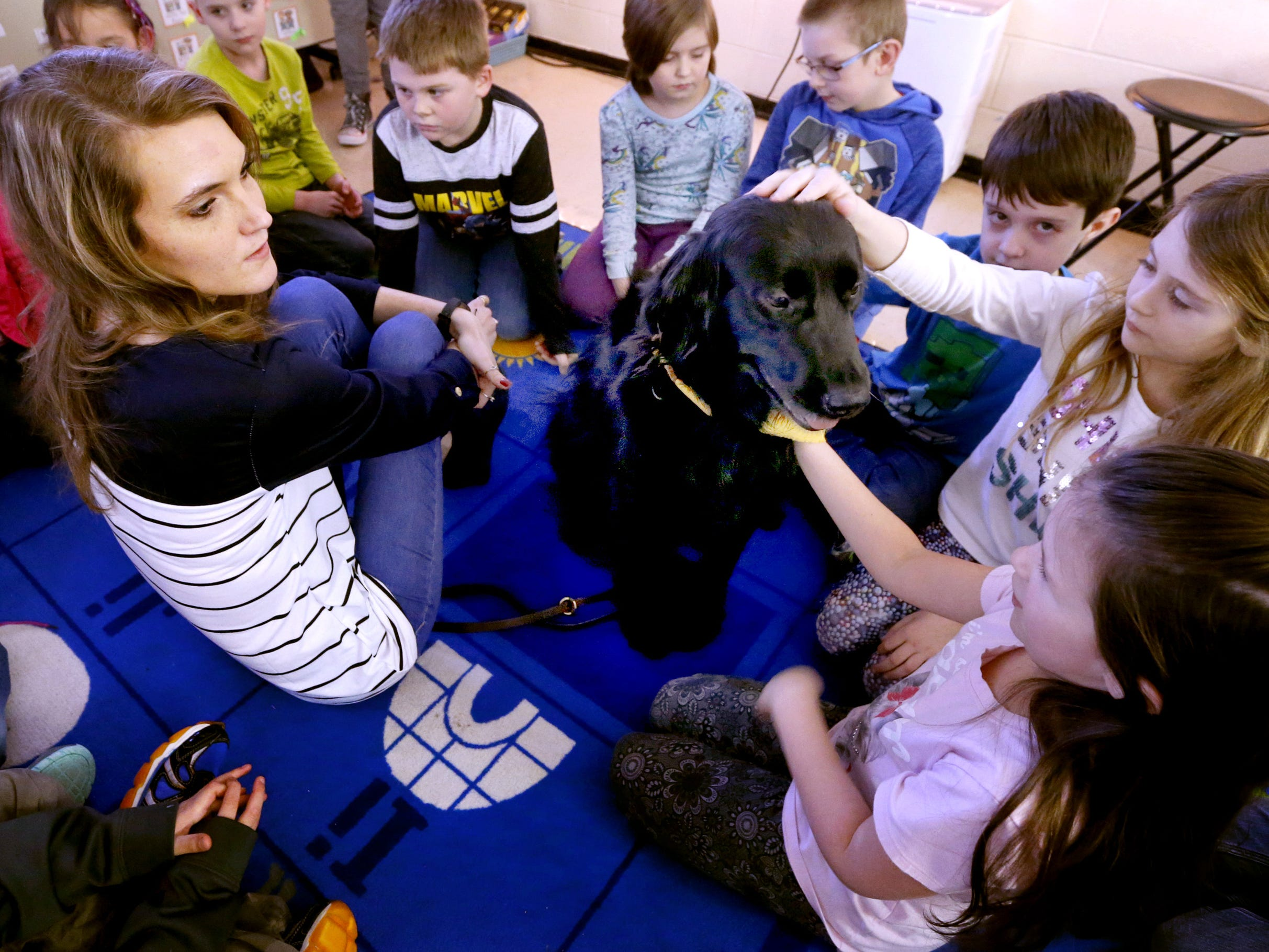 Paige Saylors a second grade teacher at Christiana Elementary, who is legally blind allows her class to gather to pet her service dog Inca on Wednesday, Jan. 24, 2018.