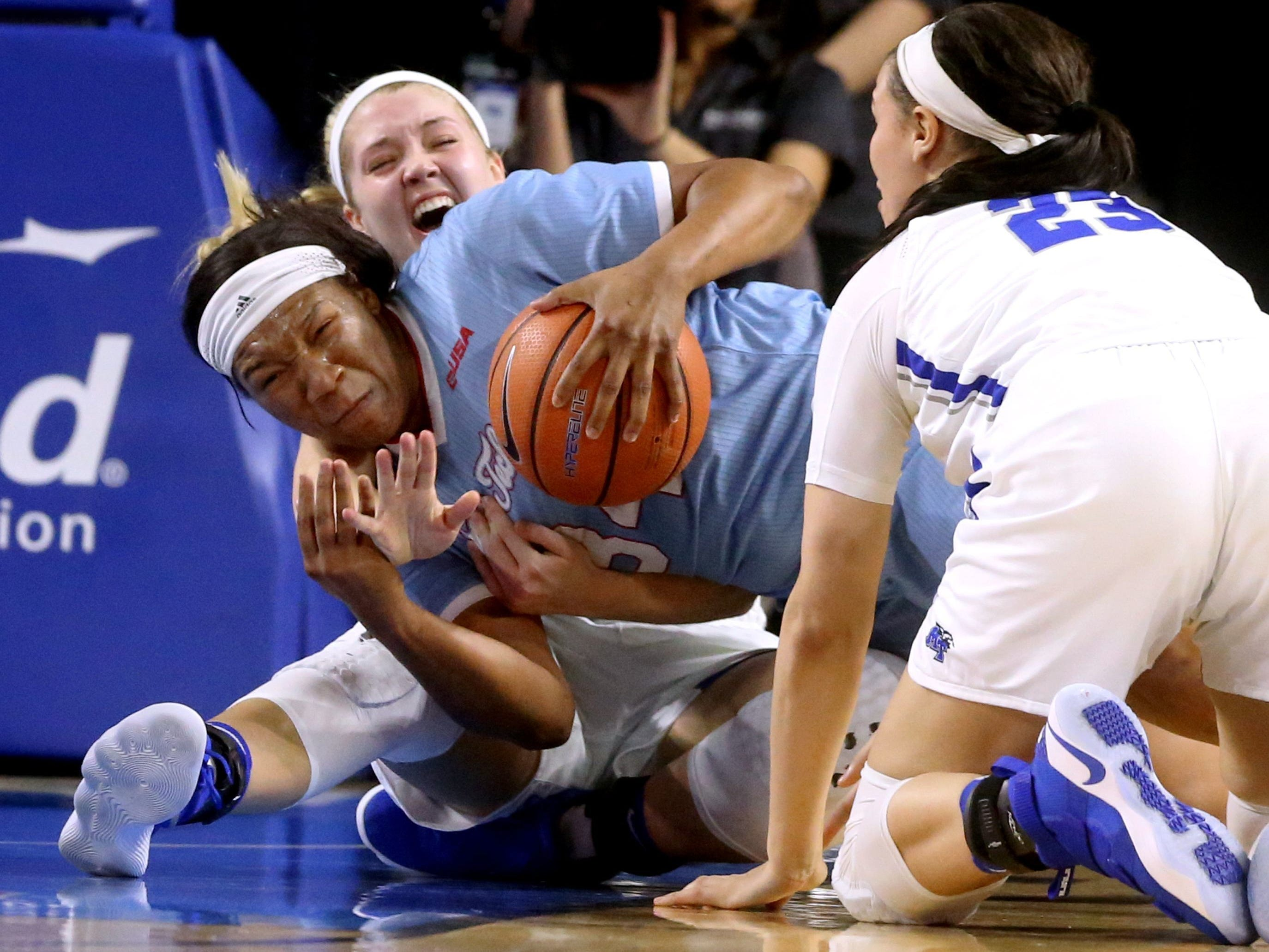 MTSU's Rebecca Reuter (24) and Gabby Lyon (23) and La Tech's Alexus Malone (34) all go after a loose ball, on Thursday, Feb. 1, 2018, at MTSU.