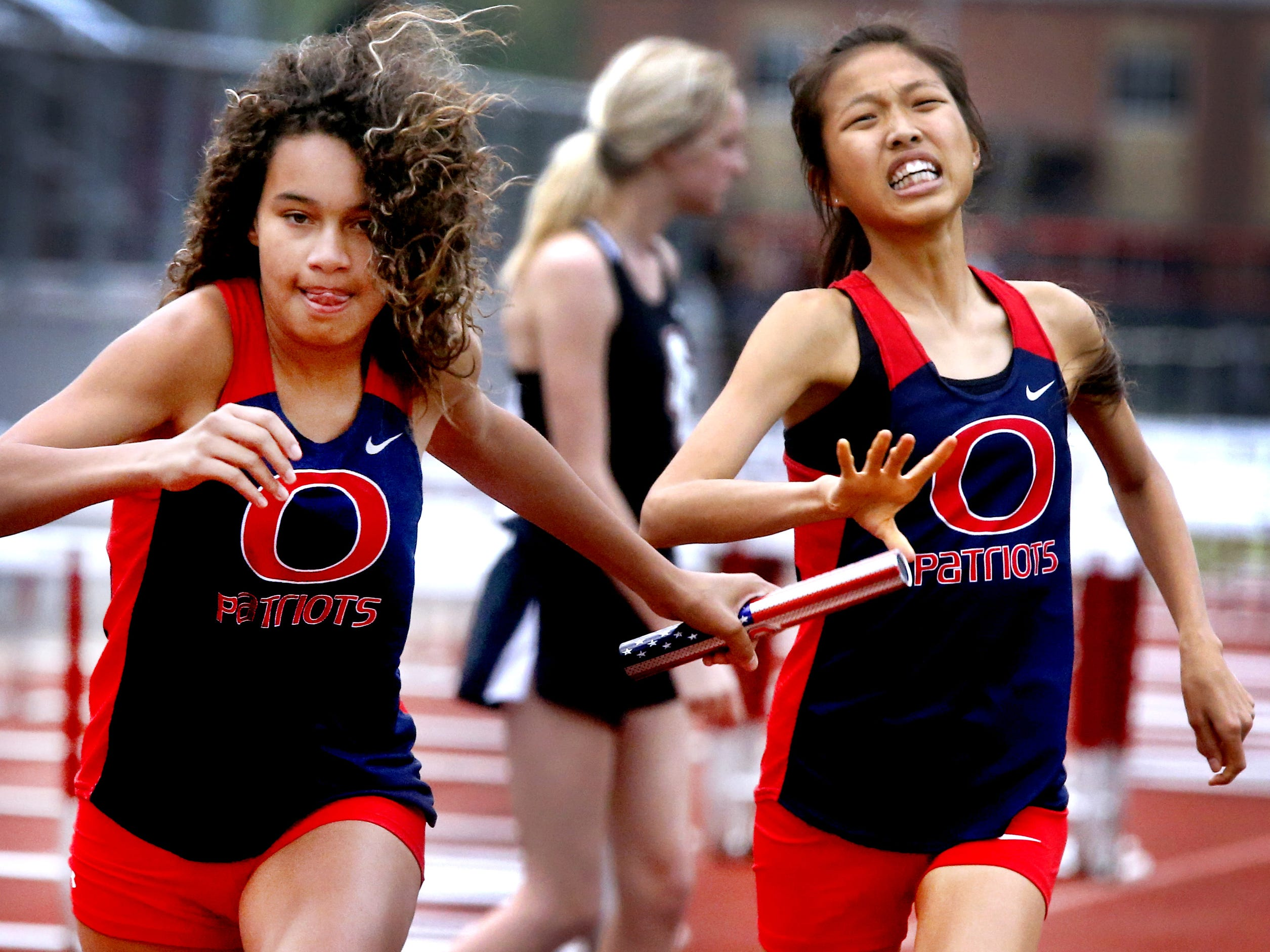 Oakland's Momo Takada, right, hands the baton off to Maja Lakes during the Girls 4x800 relay at the Rutherford County Girls Track and Field Championship at Stewarts Creek on Tuesday April 24, 2018.