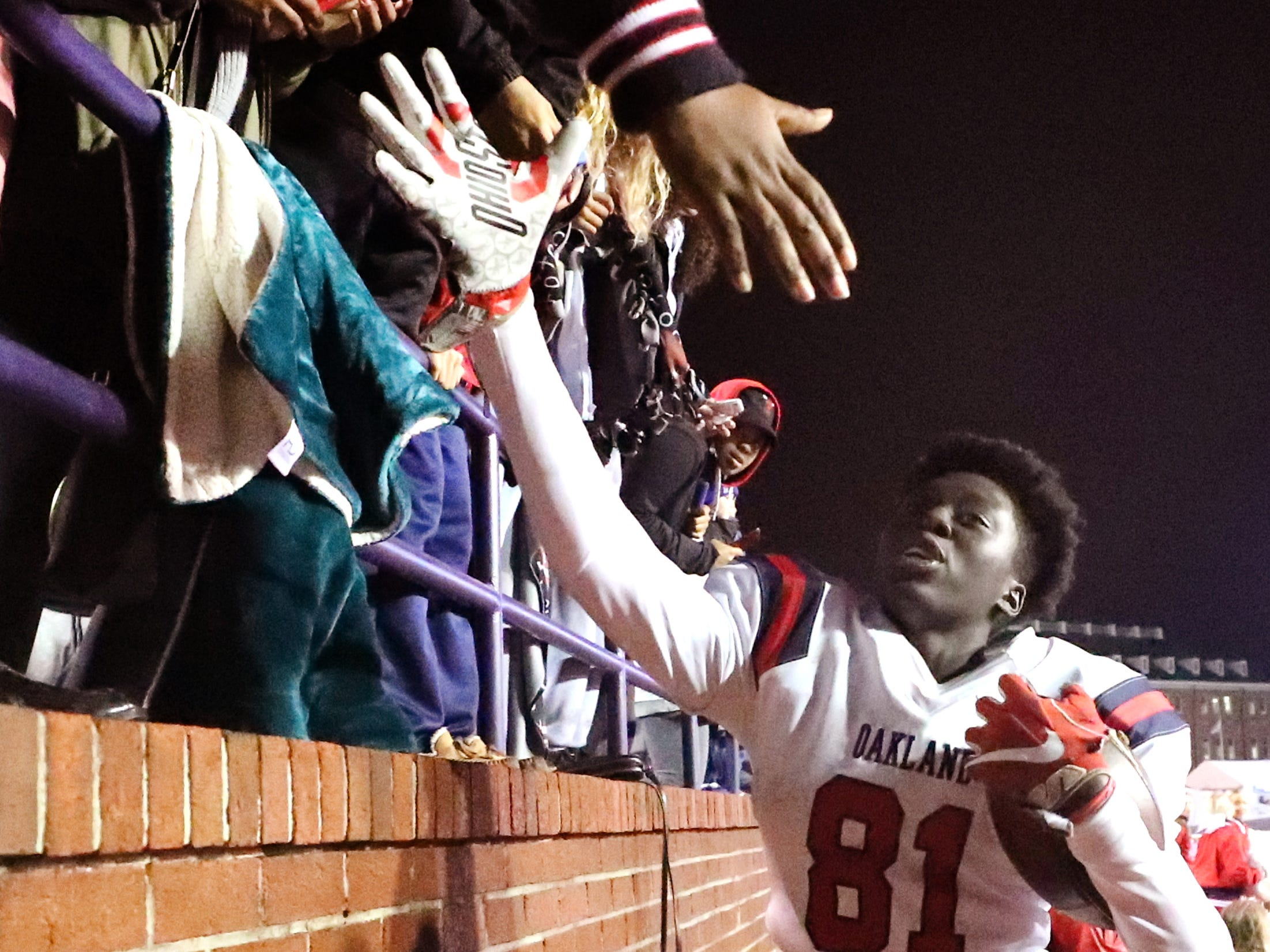 Oakland High School Dixon Luwaju (81) celebrates with fans during the final minutes of the game against Whitehaven during the 6A State Championship BlueCross Bowl game on Thursday, Nov. 29 2018. Oakland won 37-0.