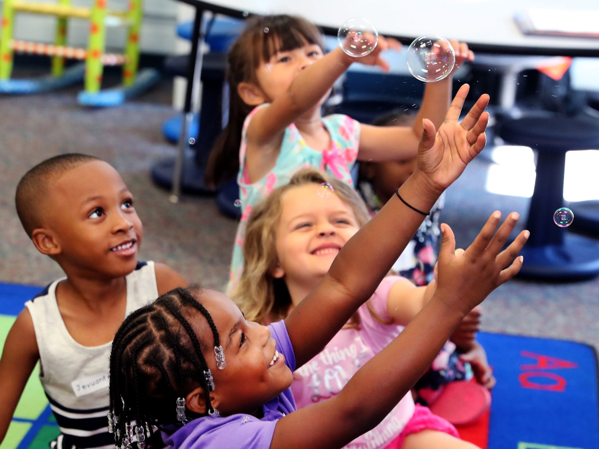 Reeves Rogers kindergarten student Lakelynn Miller reaches out to catch bubbles with other students when they are told it is ok to do so during a self discipline exercise at Kinder Camp, on Wednesday, July 18, 2018. The camp helps kindergarten students get acclimated to the classroom.