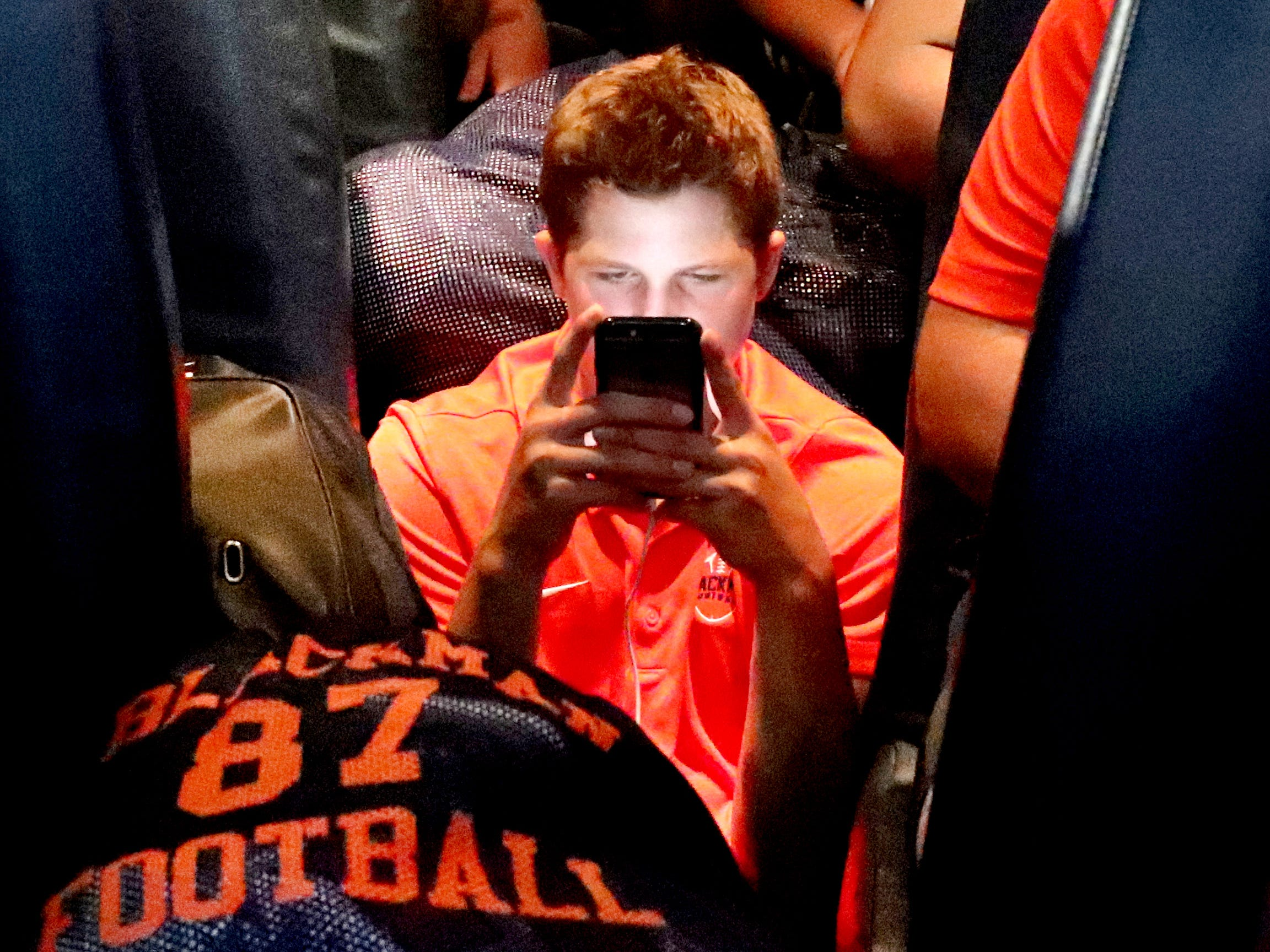 Blackman High School football player Drew Beam settles down in the isle of the bus before heading back to Blackman High School following the team's away game to play against Florence High School, on Friday Aug. 24, 2018, in Florence, Alabama.