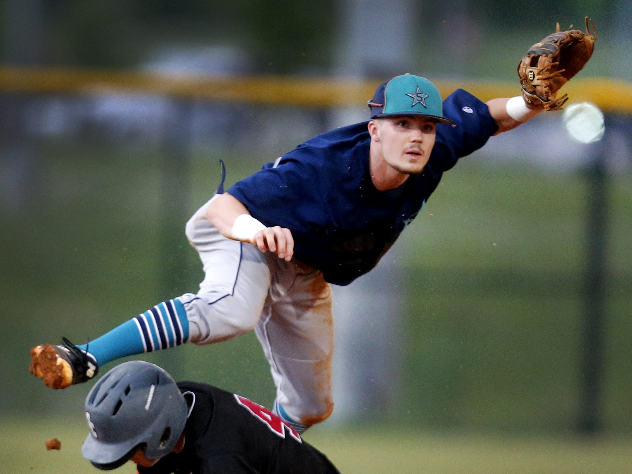 Siegel's Zach Bondurant (26) jumps over Stewarts Creek's Jake Alexander (4) after outing him and throwing to first for a double play during the Region 4-AAA baseball title game on Tuesday, May 15, 2018, at Stewarts Creek.