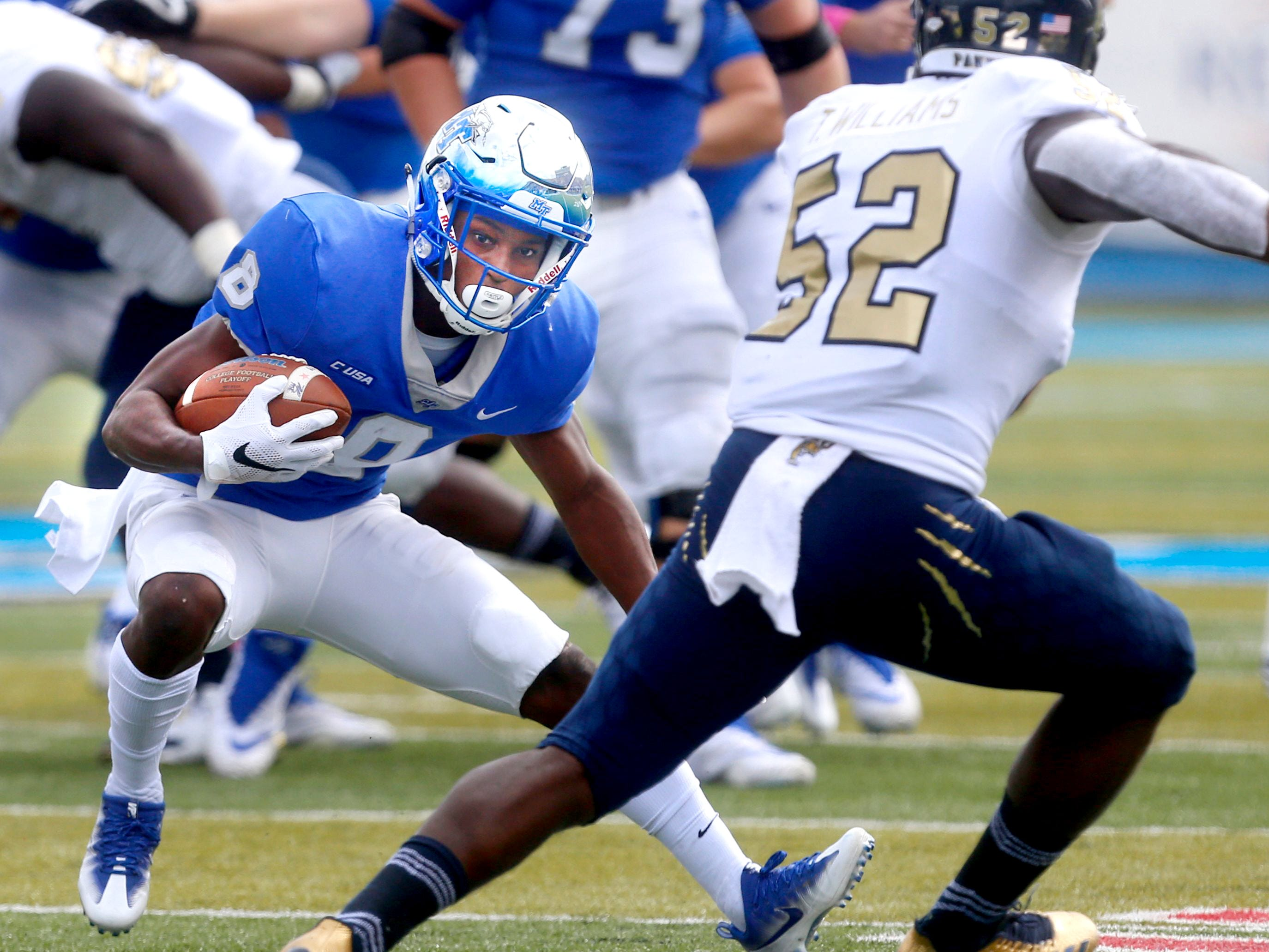 MTSU?s Ty Lee  runs the ball as FIU?s Treyvon Williams  moves in for the tackle during a game last season.