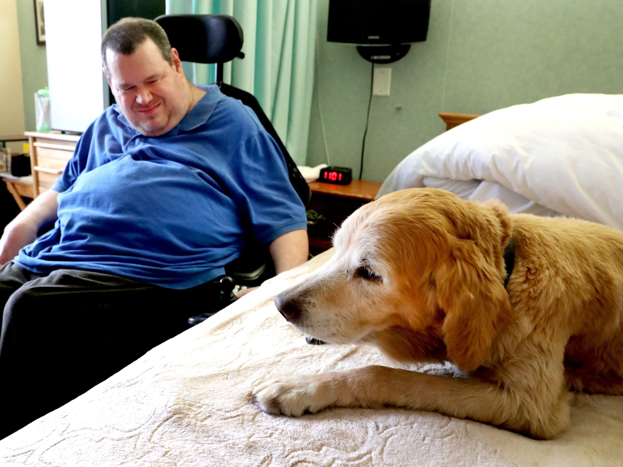JT Potts a resident at Community Care of Rutherford County hangs out with Goldie the center?s dog in his room, on Thursday, Oct. 25, 2018. Goldie has recently been diagnosed with kidney failure and Potts wrote a letter in Goldie?s voice about her time at Community Cares.