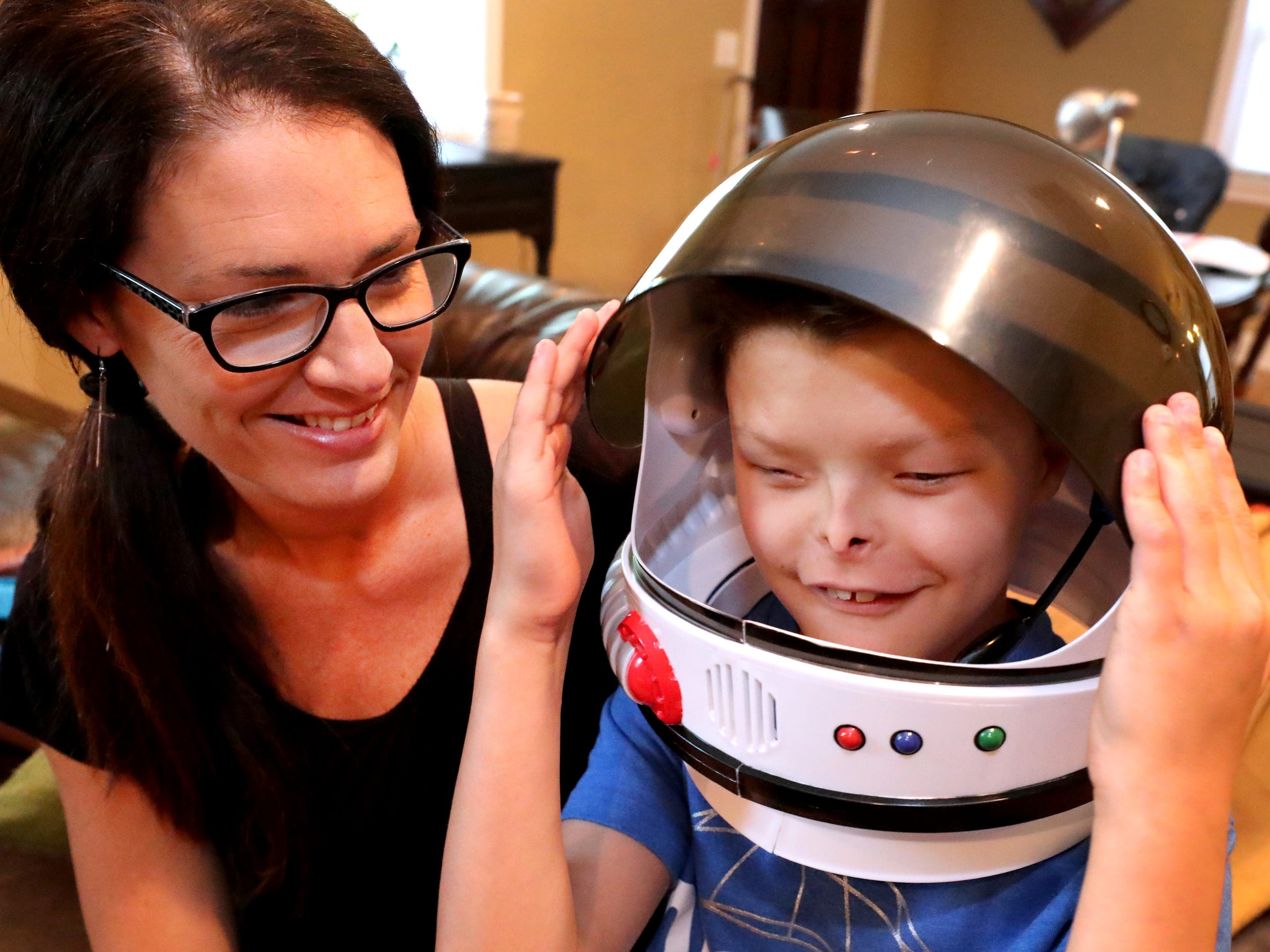 "Zaden Dill, 11 shows off his space helmet like the one worn by the lead character in the movie ""Wonder"" while sitting next to his mom Chel Dill, on Thursday, May, 31 2018.  Like the lead character in the movie Dill has undergone 60 plus surgeries."