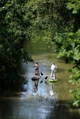 Bert and Lisa Mckeand of Franklin use standup paddle boards to travel down the Harpeth River in Franklin on June 25, 2017.