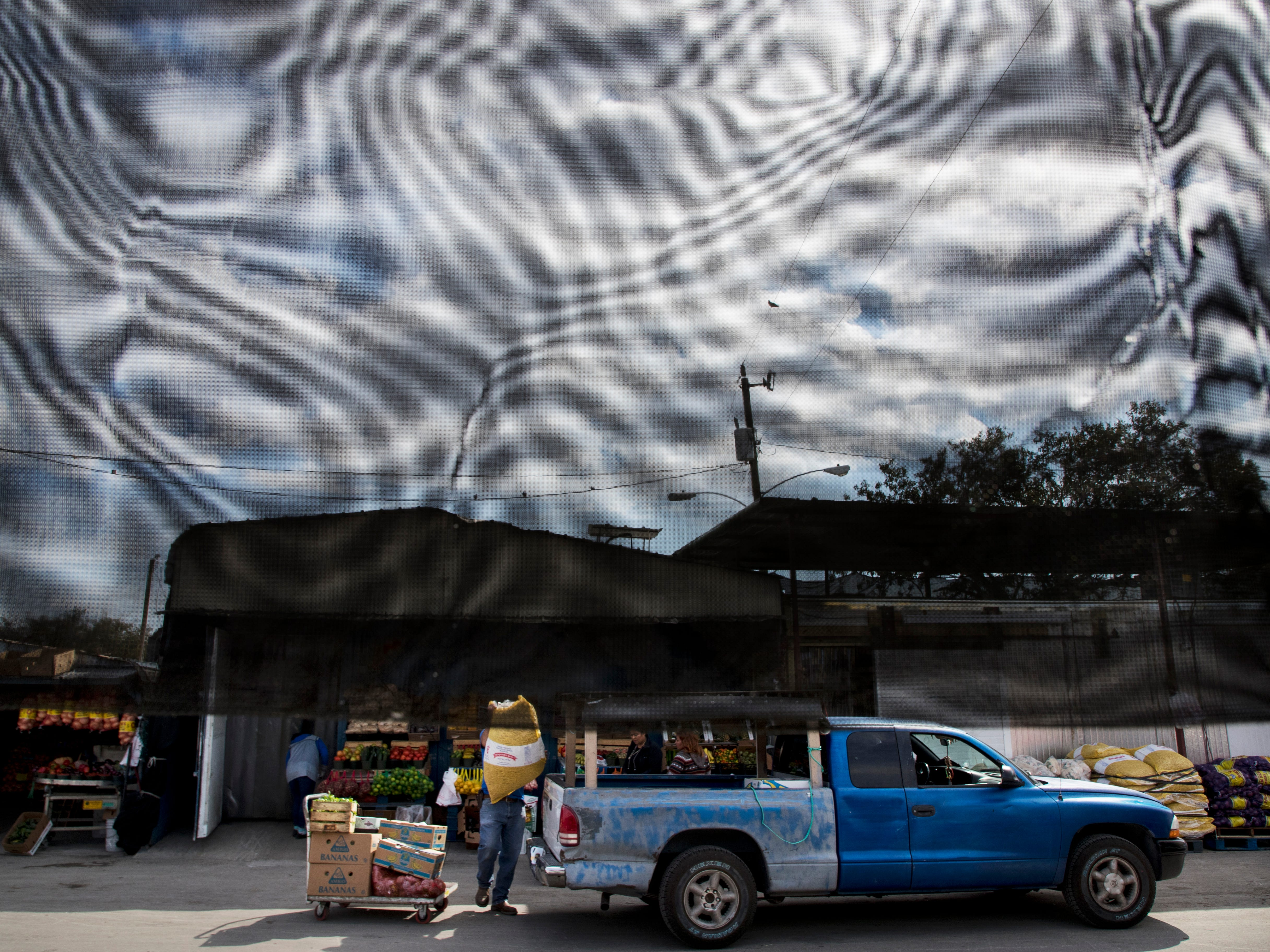 Produce is transferred to an awaiting customer at the Farmer's Market in Immokalee on Thursday 1/31/2019.