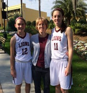 Amanda (left) and Emily Lines (right) played together for their mother, Jen Lines (center), on the 2014-15 First Baptist Academy girls basketball team. Though one of the sisters was on the team all 10 seasons Lines coached at FBA, 2014-15 was the only season they played together. Amanda was in eighth grade and Emily was a senior.