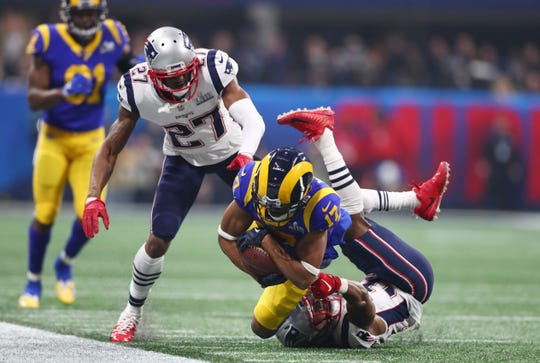 Los Angeles Rams wide receiver Robert Woods (17) is tackled by New England Patriots defensive back Jonathan Jones (31) and defensive back J.C. Jackson (27) of Immokalee in the fourth quarter in Super Bowl LIII at Mercedes-Benz Stadium on Sunday in Atlanta.