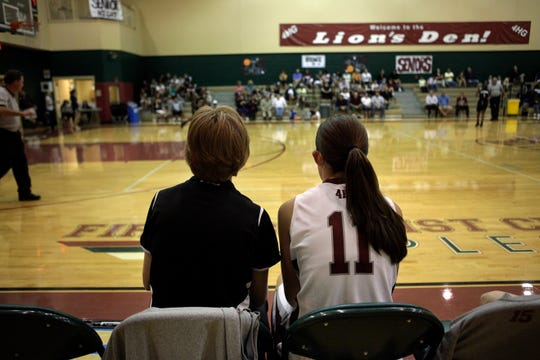First Baptist Academy girls basketball coach Jen Lines sits with her daughter Emily during a game in 2013. Lines, who is resigning after this season, coached one of her two daughters in all 10 seasons at FBA. Emily and Amanda Lines were on the same team playing for their mom in 2014-15.