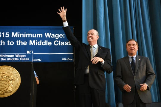 Gov. Phil Murphy with NJ house speaker Craig Coughlin, waves to a full house prior to signing a bill raising New Jersey's minimum wage to $15 an hour during a ceremony at headquarters of immigrant advocacy group Make The Road NJ in Elizabeth on Monday, February 4, 2019. The minimum wage will raise incrementally to $15 an hour in 2024.