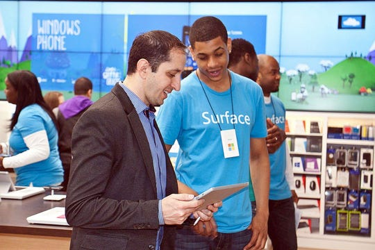 In this file photo from May 5, 2014, Surface chief designer Pete Kyriacou shows an associate its features at the opening of the Microsoft Garden State Plaza location.